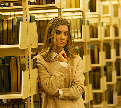 Elena pensively leans against a bookshelf in the academic section of a public library.
