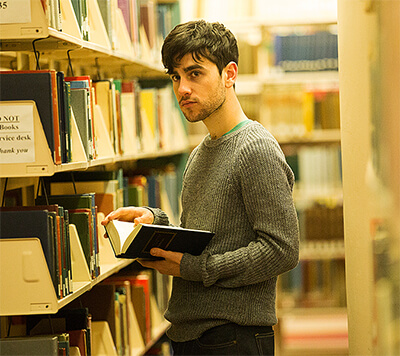 Rodrigo stands, holding a book but looking elsewhere, by a bookshelf in the academic section of a public library.