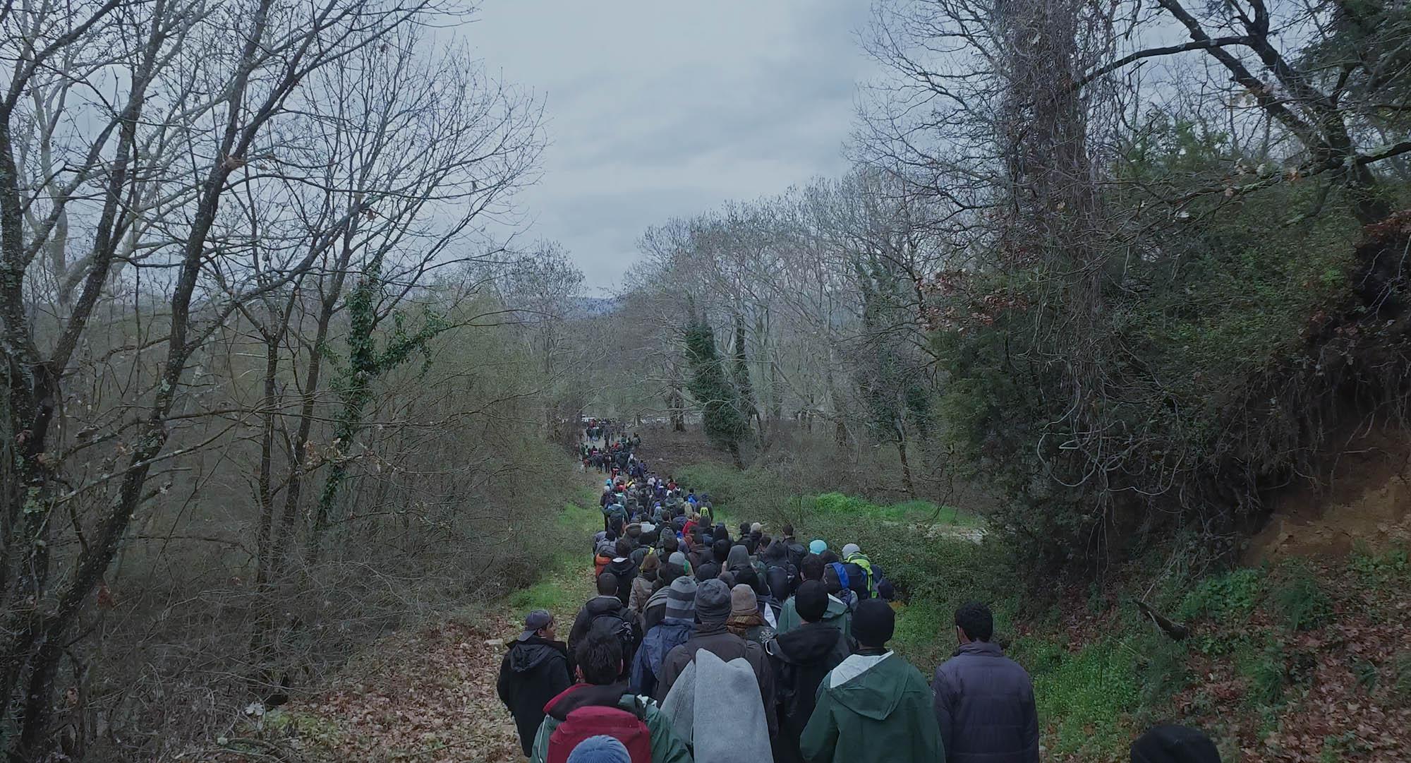 Refugees walking near Idomeni Camp, Greece in HUMAN FLOW, an Amazon Studios release. Photo courtesy of Amazon Studios.