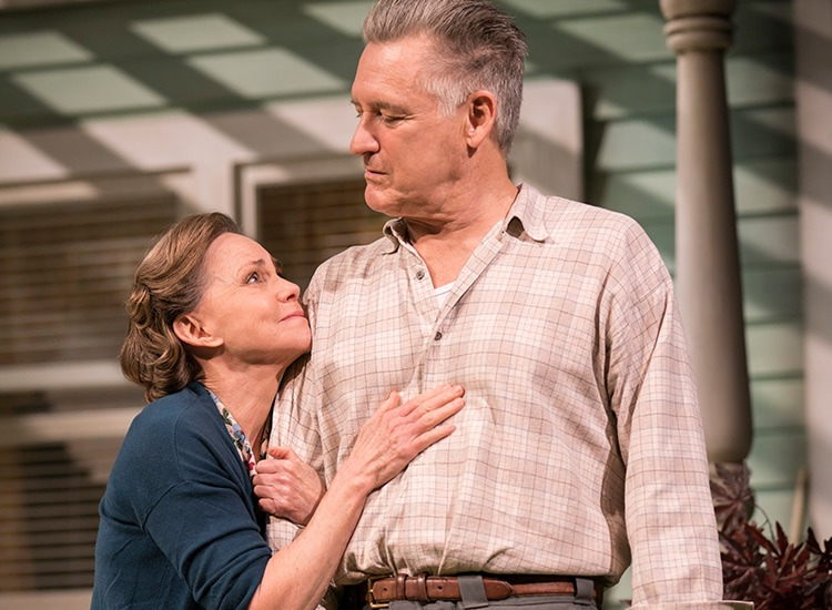 Production photograph of Sally Field and Bill Pullman as Kate and Joe Keller in a fond embrace, on the porch of the Keller's house.