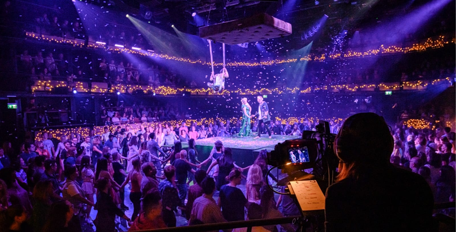 A photograph of the camera rehearsal for Small Island, featuring a camera operators filming three actors standing on stage.