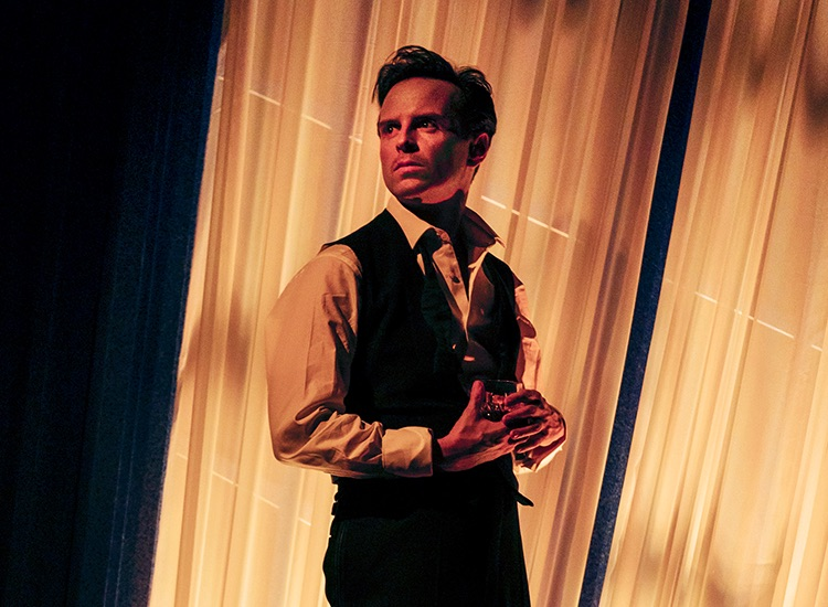 Production photography of Andrew Scott as star actor Gary Essendine holding a glass in his apartment.