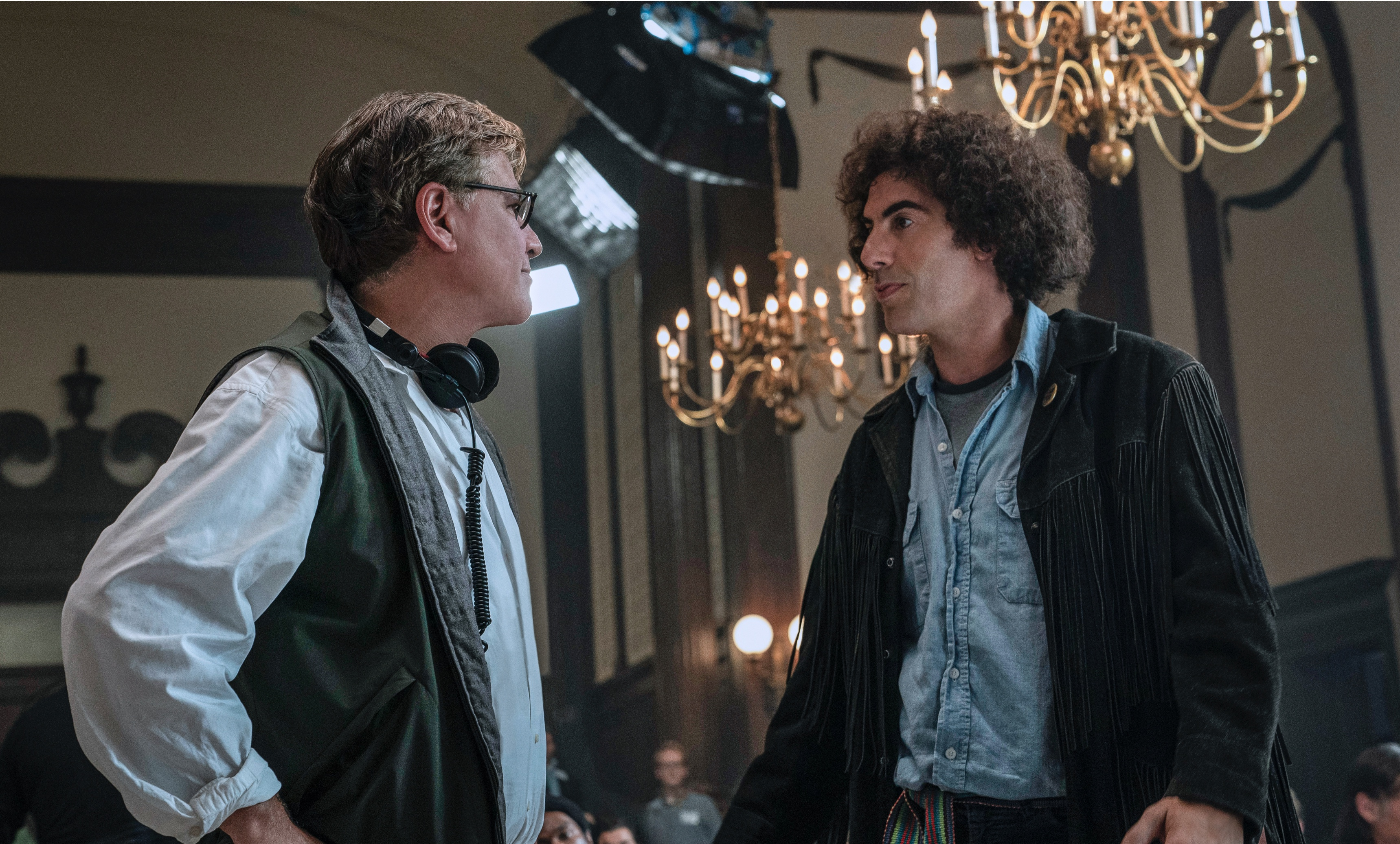 Aaron Sorkin directs Sacha Baron Cohen between takes for The Trial of the Chicago 7.