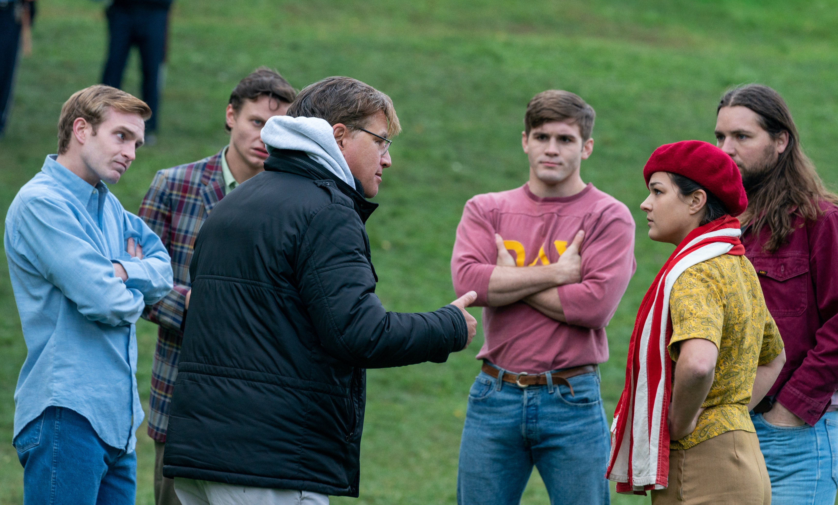 Extras circle around Aaron Sorkin as he prepares them for a protest scene in The Trial of the Chicago 7.