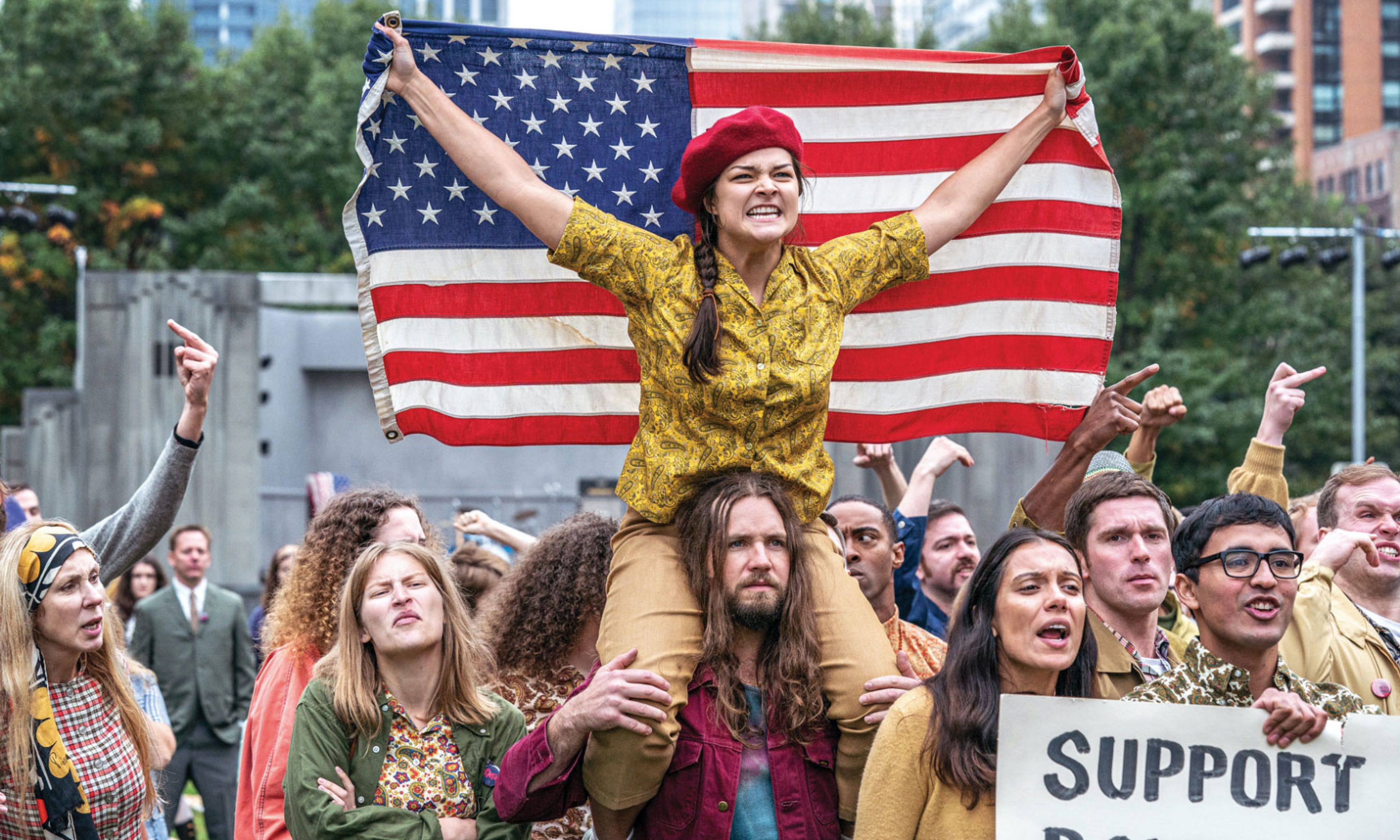 In this crowd scene, a young woman sits on a long-haired protester's shoulders, wearing a red beret and holding an American flag outstretched.