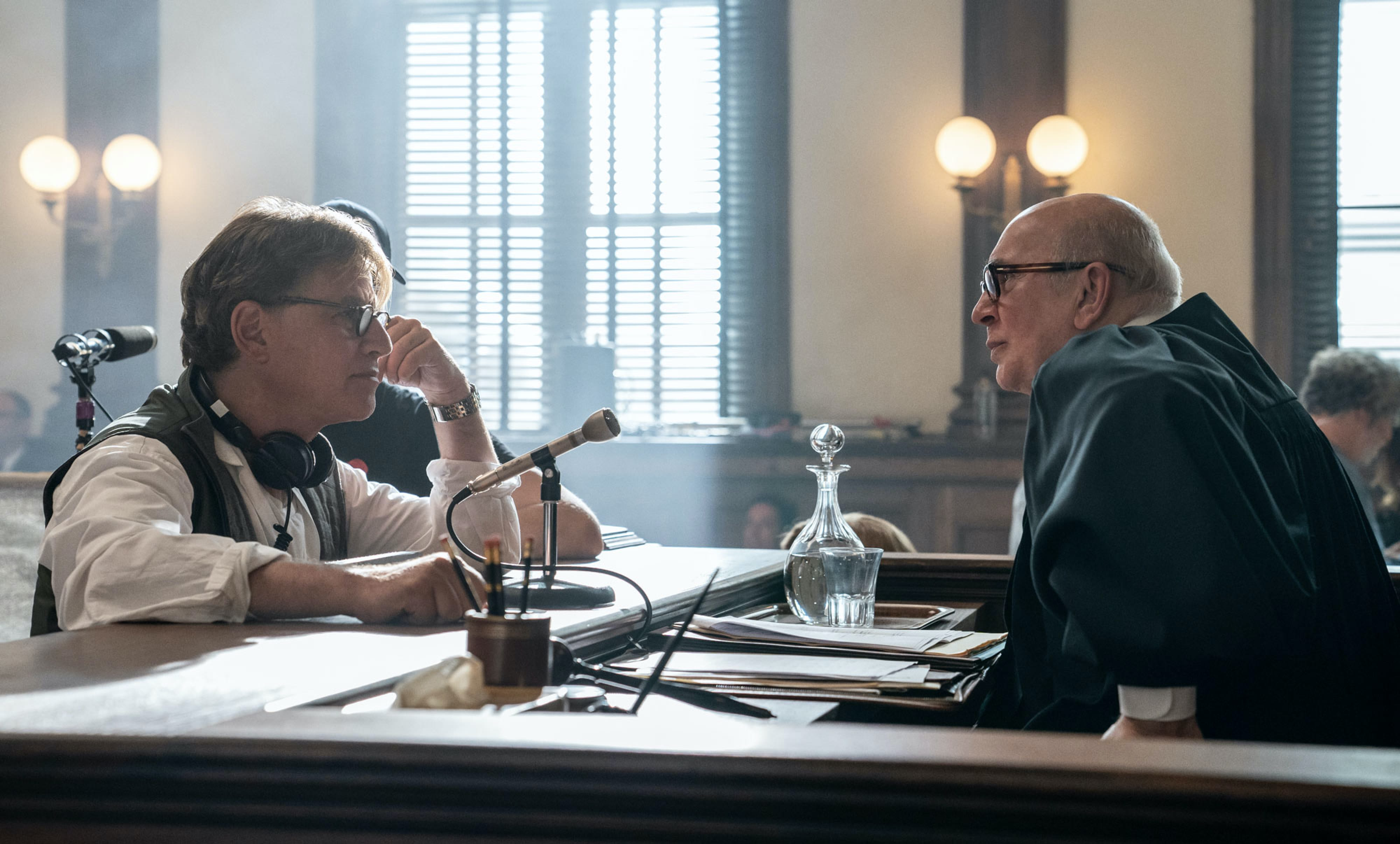 On the courtroom set, Sorkin has approached the bench to speak with Frank Langella, in costume as Judge Julius Hoffman.