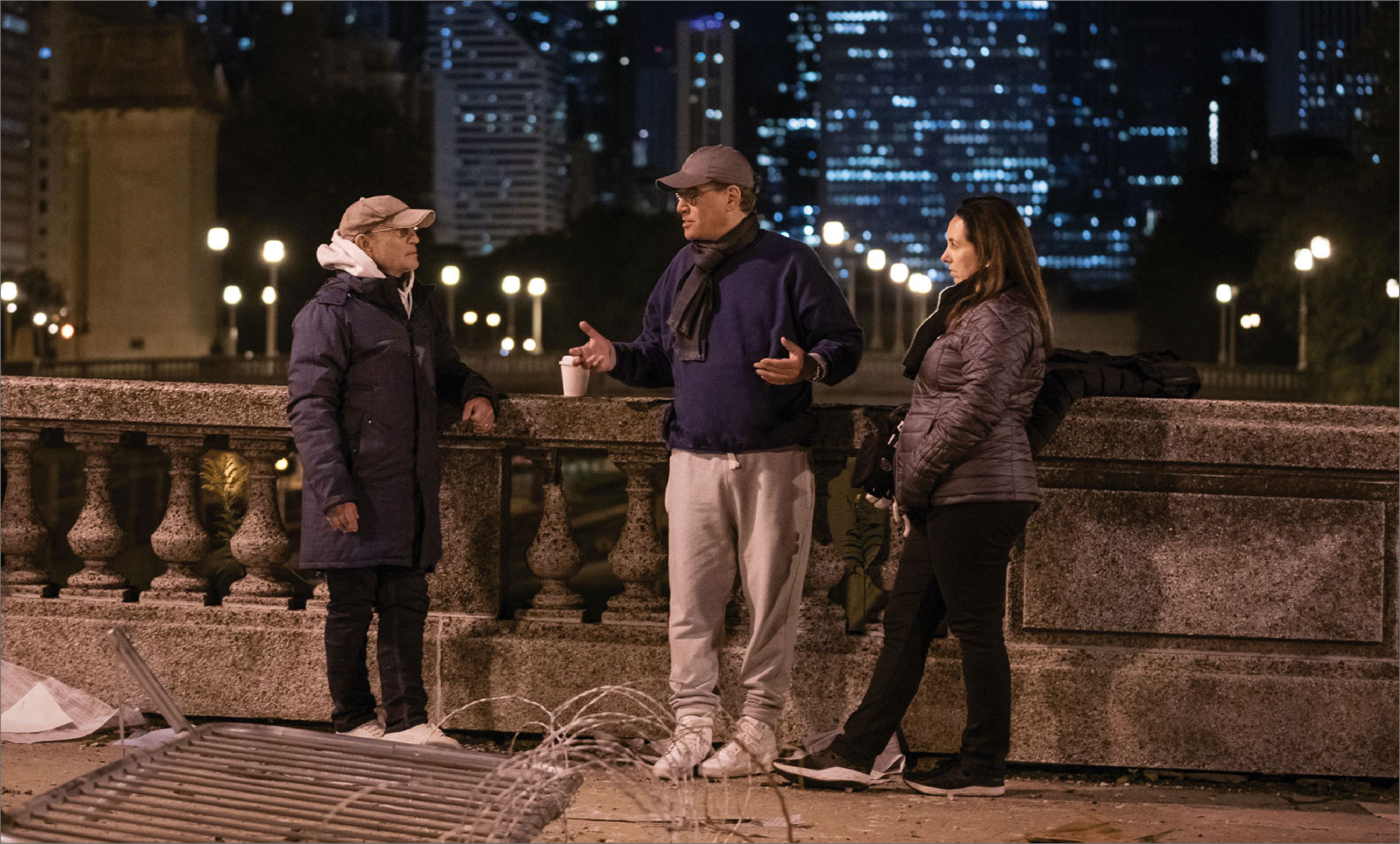 Sorkin stands on a bridge with a crew member on either side of him. Chicago highrises are illuminated in the background.