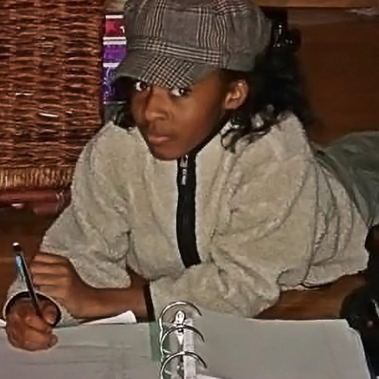 A throwback photo of Ayo Edebiri as a middle schooler, doing her homework in a large binder, looking oh so excited to be doing schoolwork.