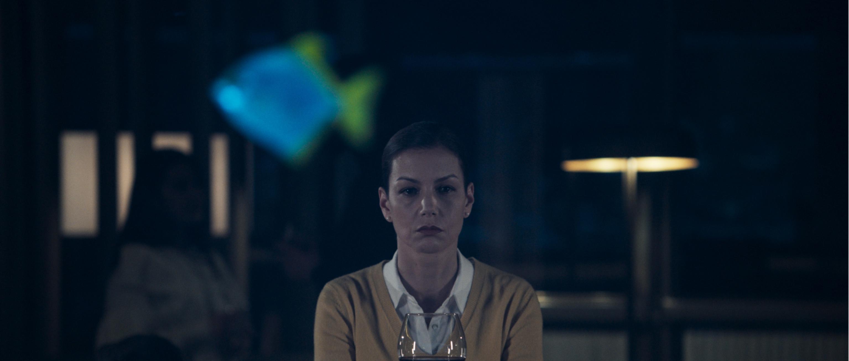 Peri, bir akvaryumun arkasına oturmuş, bir kadeh şarabıyla düşüncelere dalmış gözüküyor.