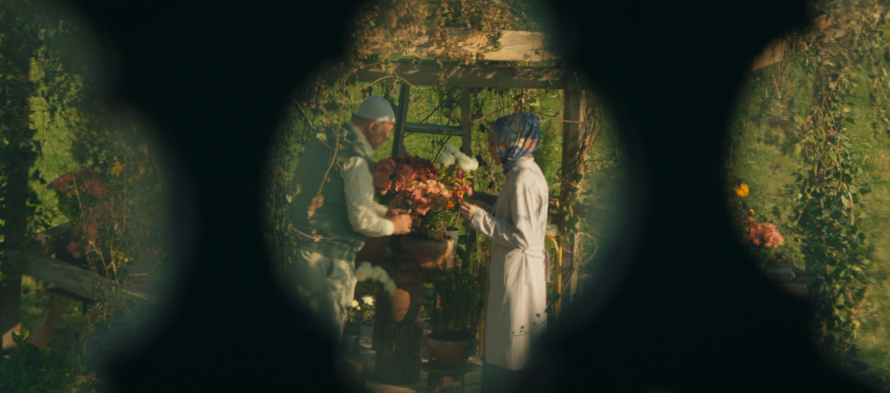 Meryem ve Hoca, cennet gibi yeşil bir bahçede çiçek ekimi üzerine tartışırken, bir çitin arkasından konuşurken görülüyor.