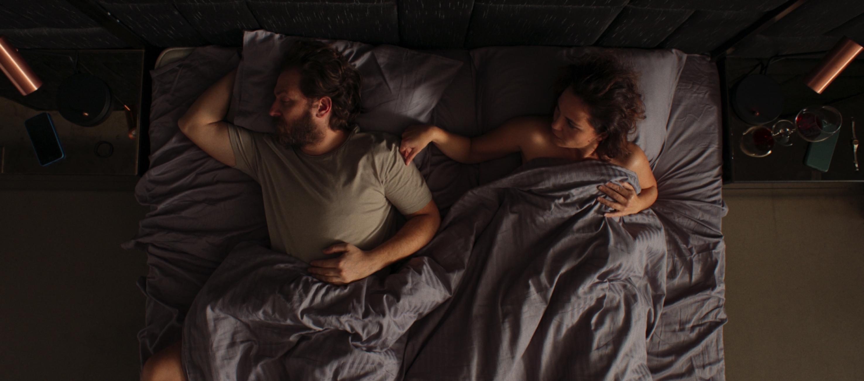 Sinan ve Gülbin üzerlerine gri bir battaniye çekilmiş bir yatakta yatıyor.