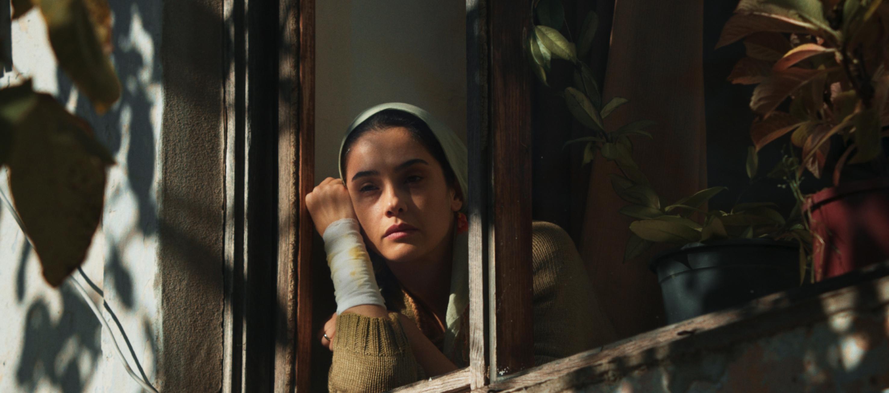 Ruhiye, kolu bandajlı bir hâlde camdan dışarı bakıyor.