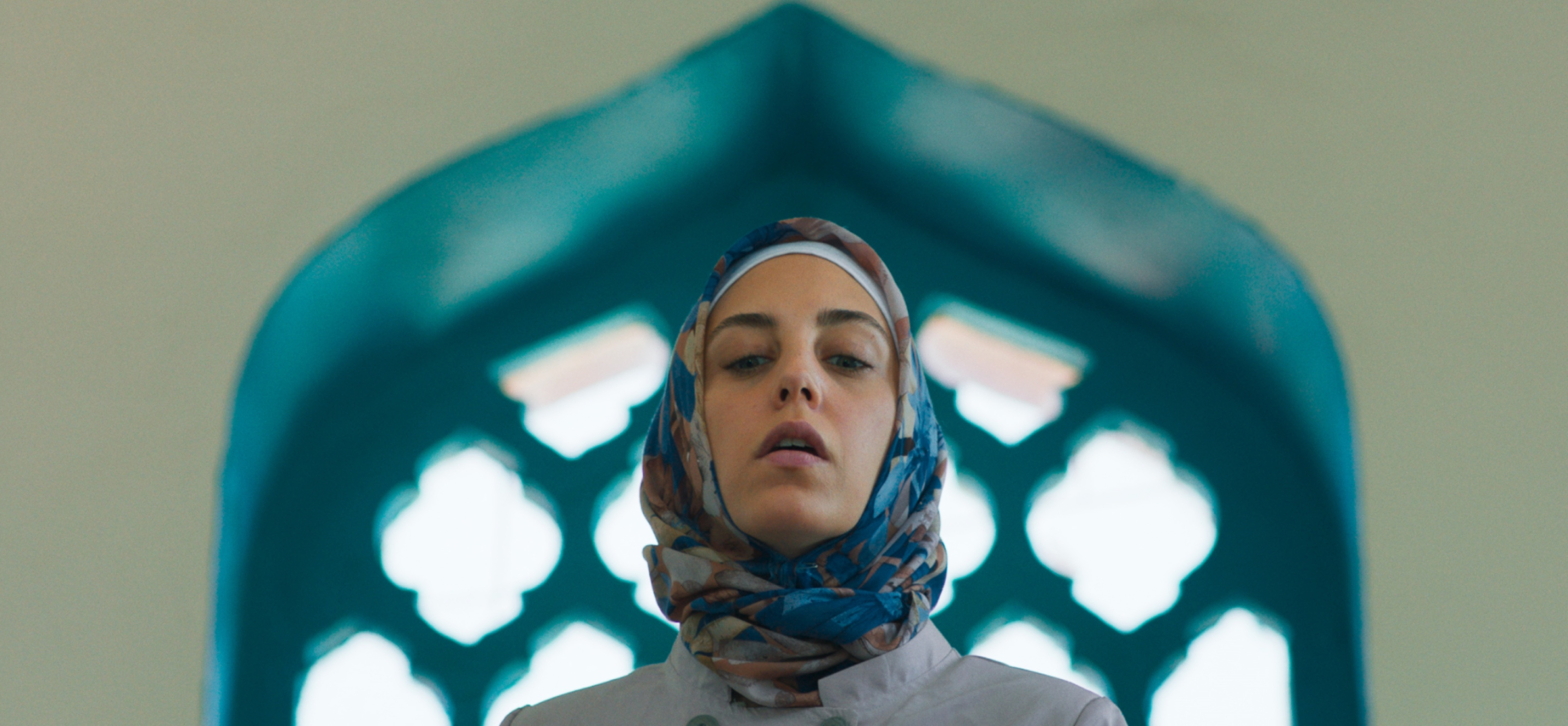 Bir Başkadır'ın bu karesinde Meryem (Öykü Karayel), mavi çerçeveli kemerli bir pencerenin önünden aşağı doğru bakıyor. Turkuaz tonlarındaki mimari yapıyla bütünleşen bir başörtüsü takıyor.