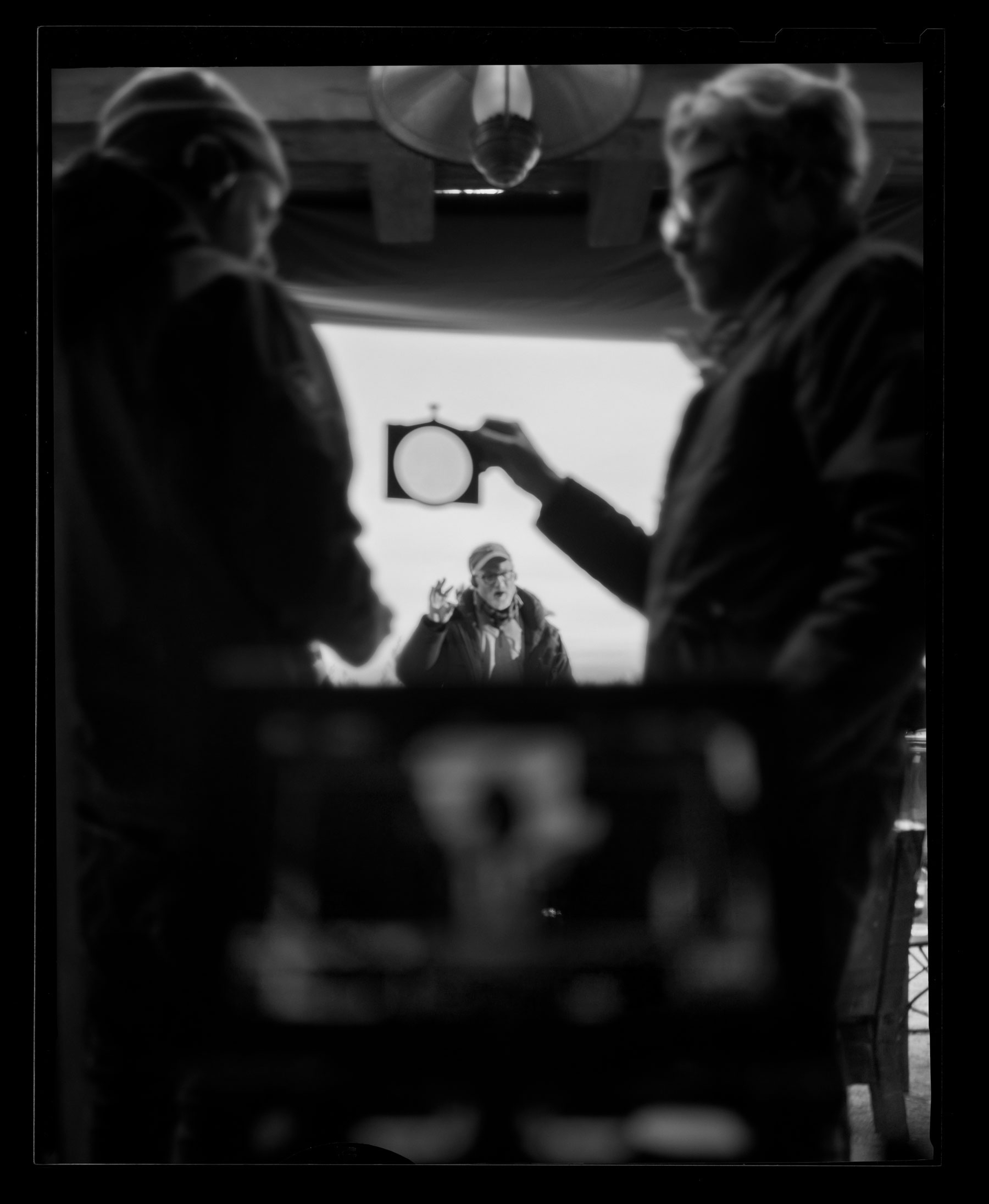 Fincher and Messerschmidt hold up a lens in this behind-the-scenes shot.