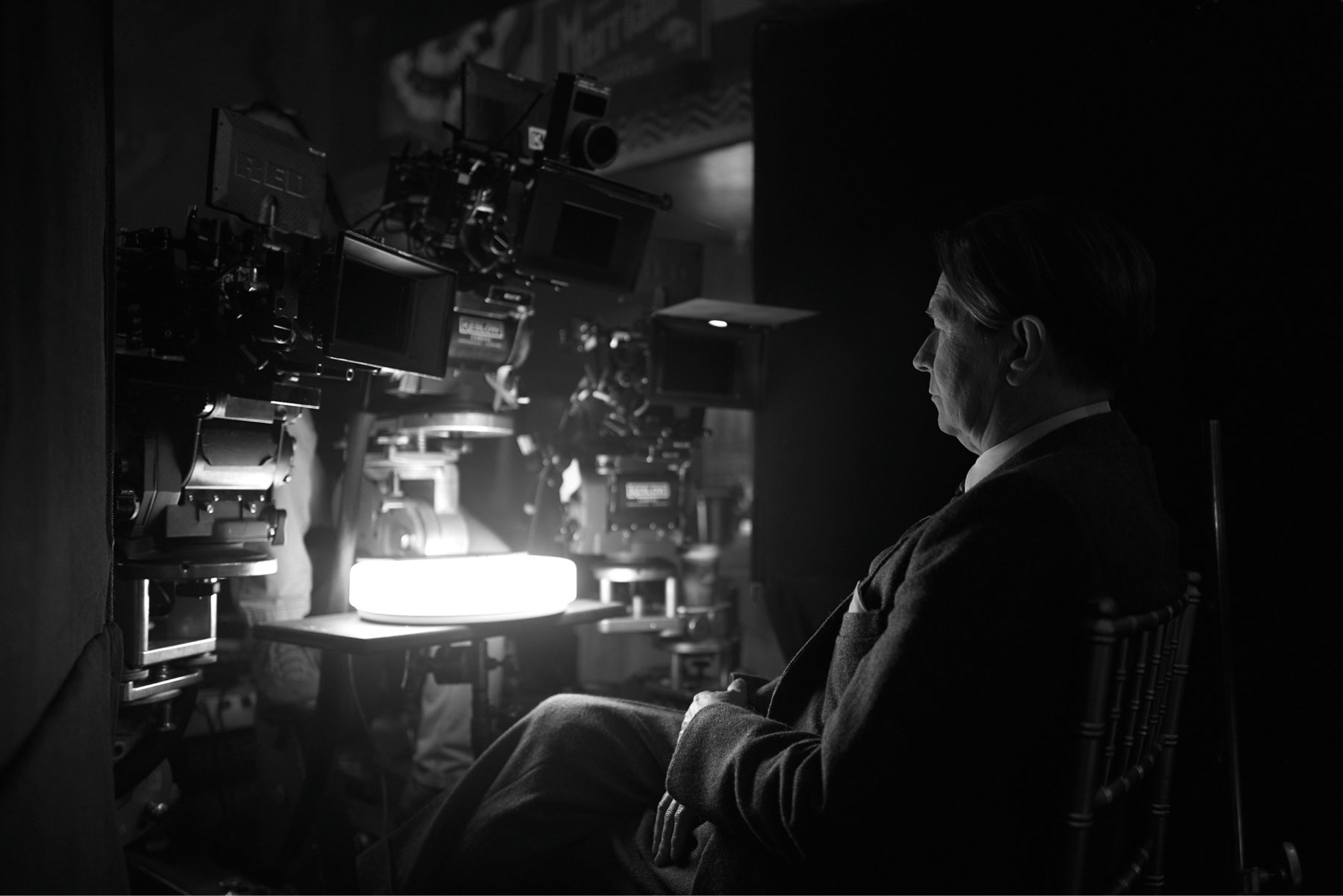 Gary Oldman in costume as Herman J. Mankiewicz sits behind a series of cameras on the set of Mank.