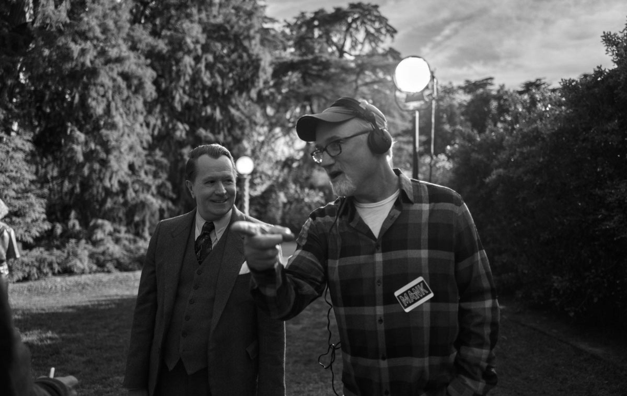 """Fincher directs Oldman on the San Simeon set. Oldman is in costume in a suit, while Fincher sports headphones and a flannel shirt on which he's stuck a sticker reading """"Mank."""""""