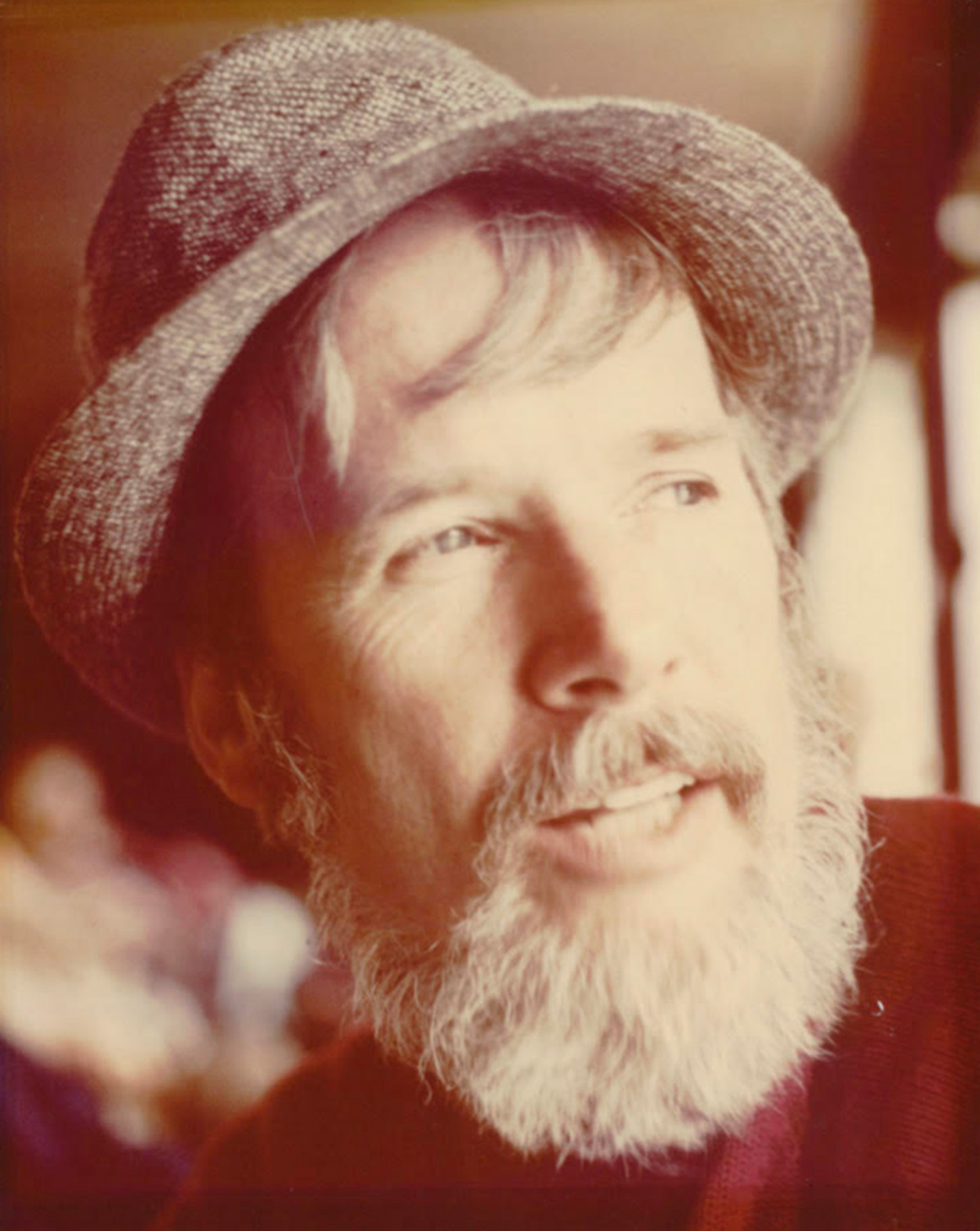 Jack Fincher sports a white beard and moustache, plus a fedora, in this sepia-toned photograph.