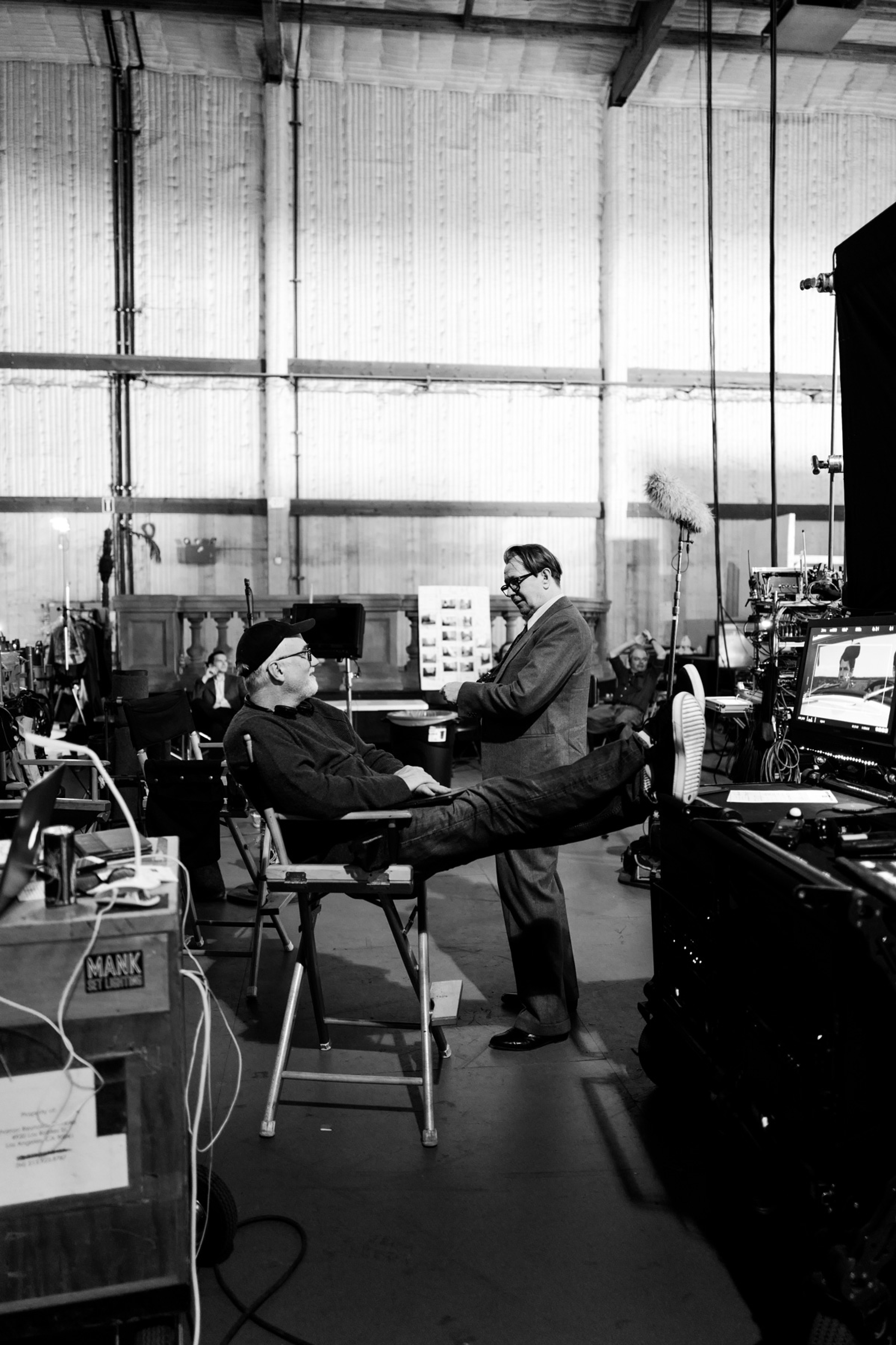 Fincher and Oldman have a chat. Fincher sits in his director's chair, feet up on a table. Oldman stands a few feet in front of him, in costume as Herman Mankiewicz.