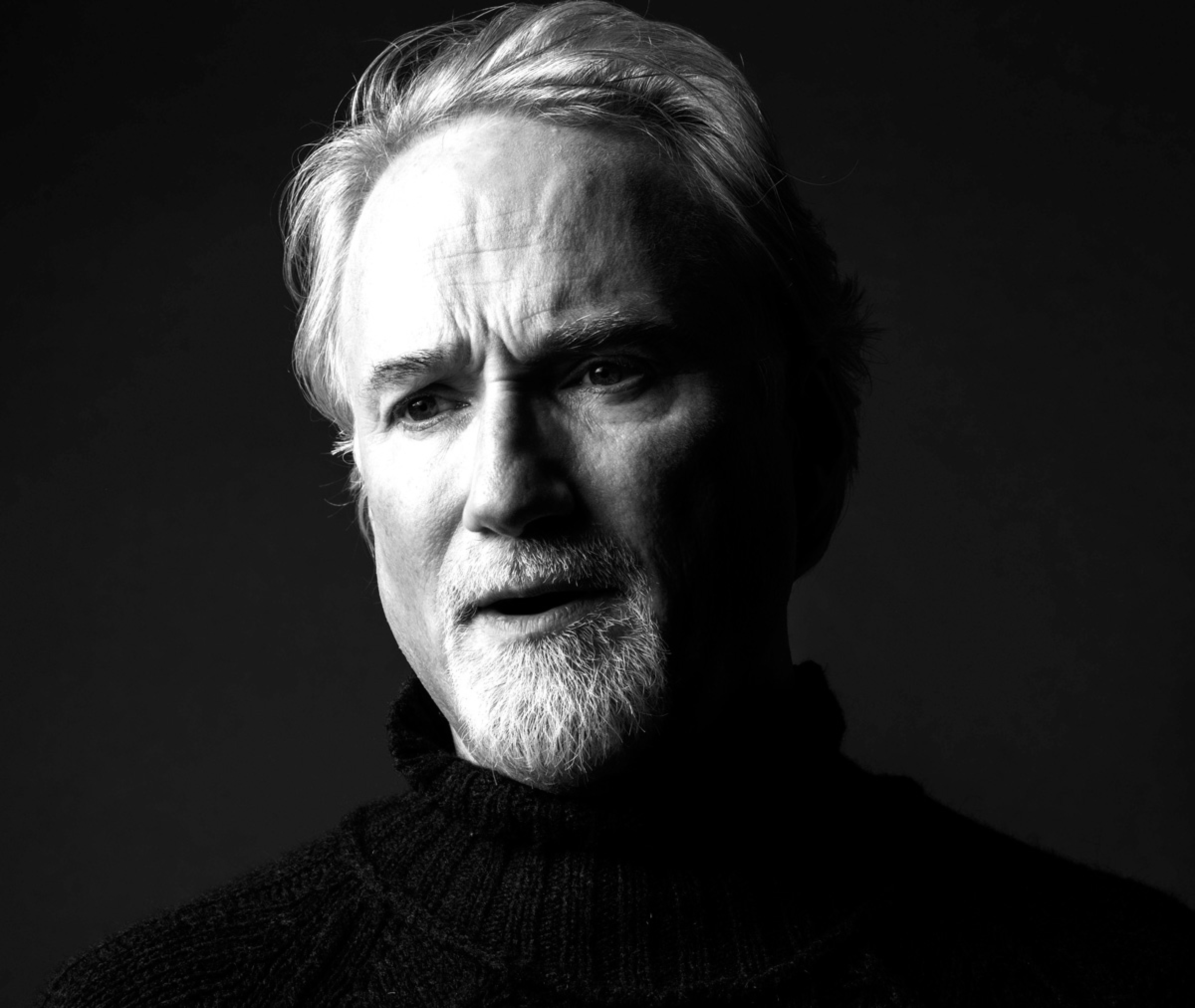 A high-contrast black-and-white portrait of David Fincher. He wears a black turtleneck and looks past the camera.