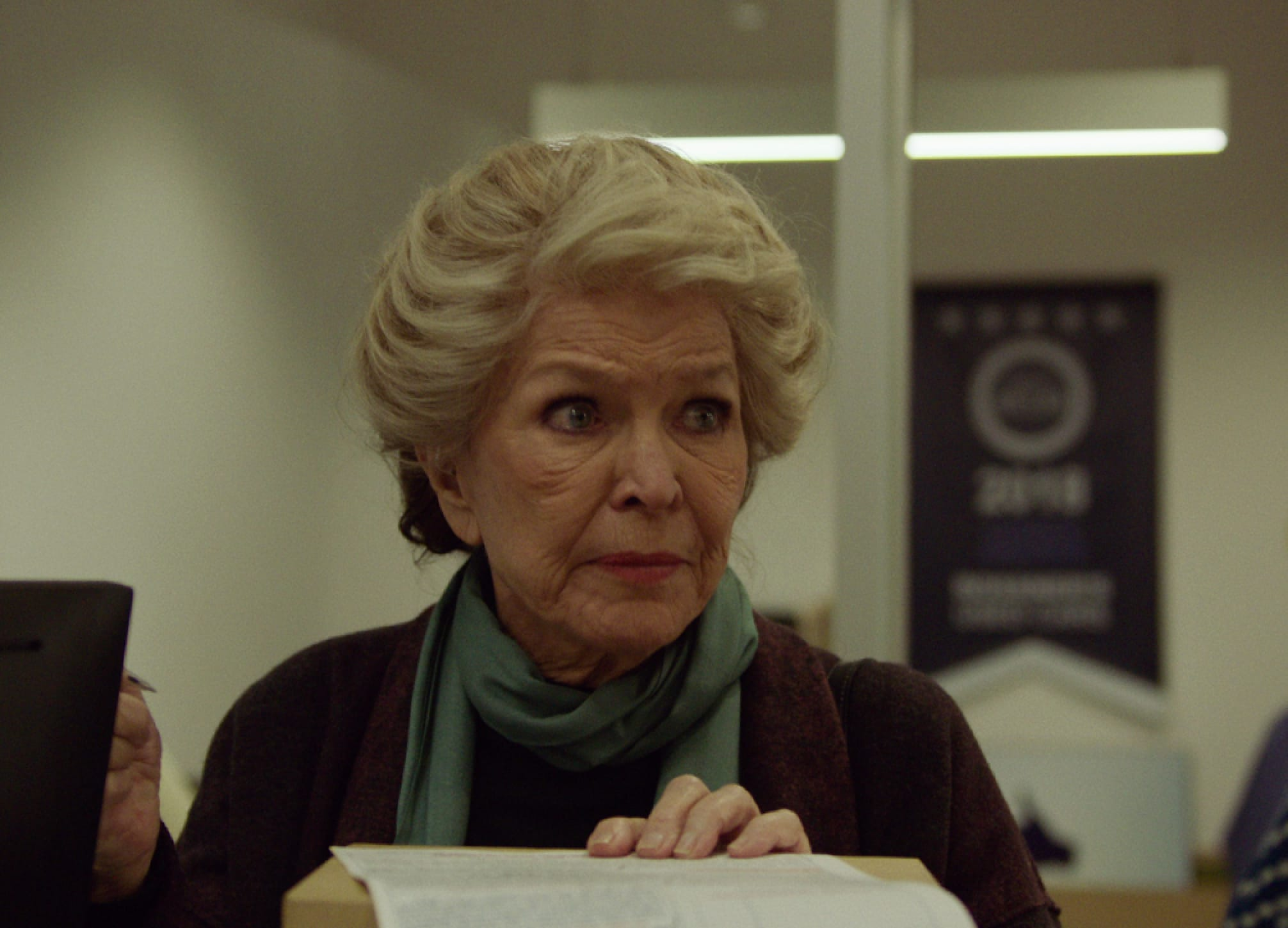 Ellen Burstyn as Elizabeth Weiss in a still from Pieces of a Woman. Her large blue eyes match the thin scarf tied around her neck, and her white hair is styled in an elegant up-do.