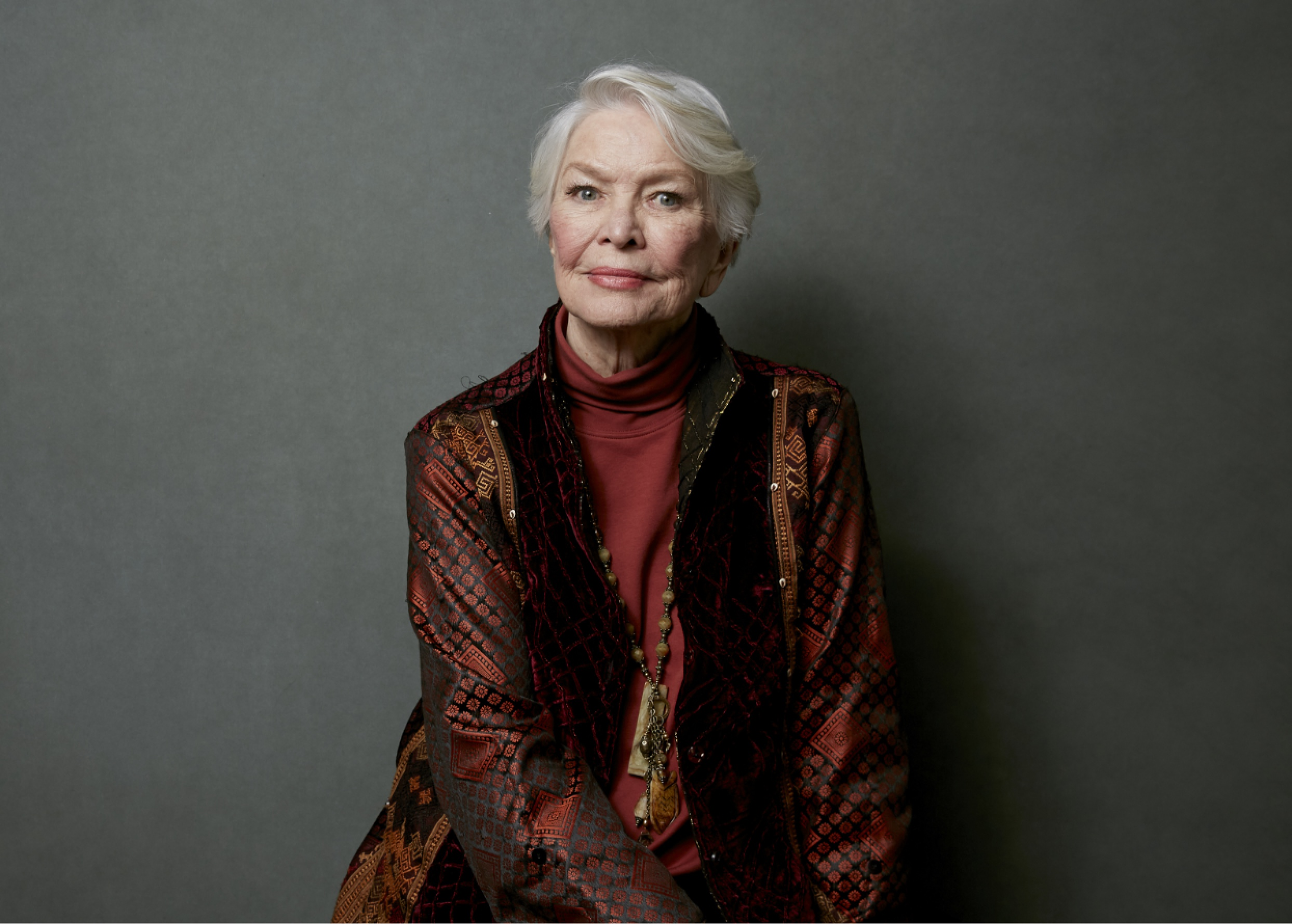 A portrait of Ellen Burstyn, smiling and looking elegant with close-cropped hair and a red jacket.