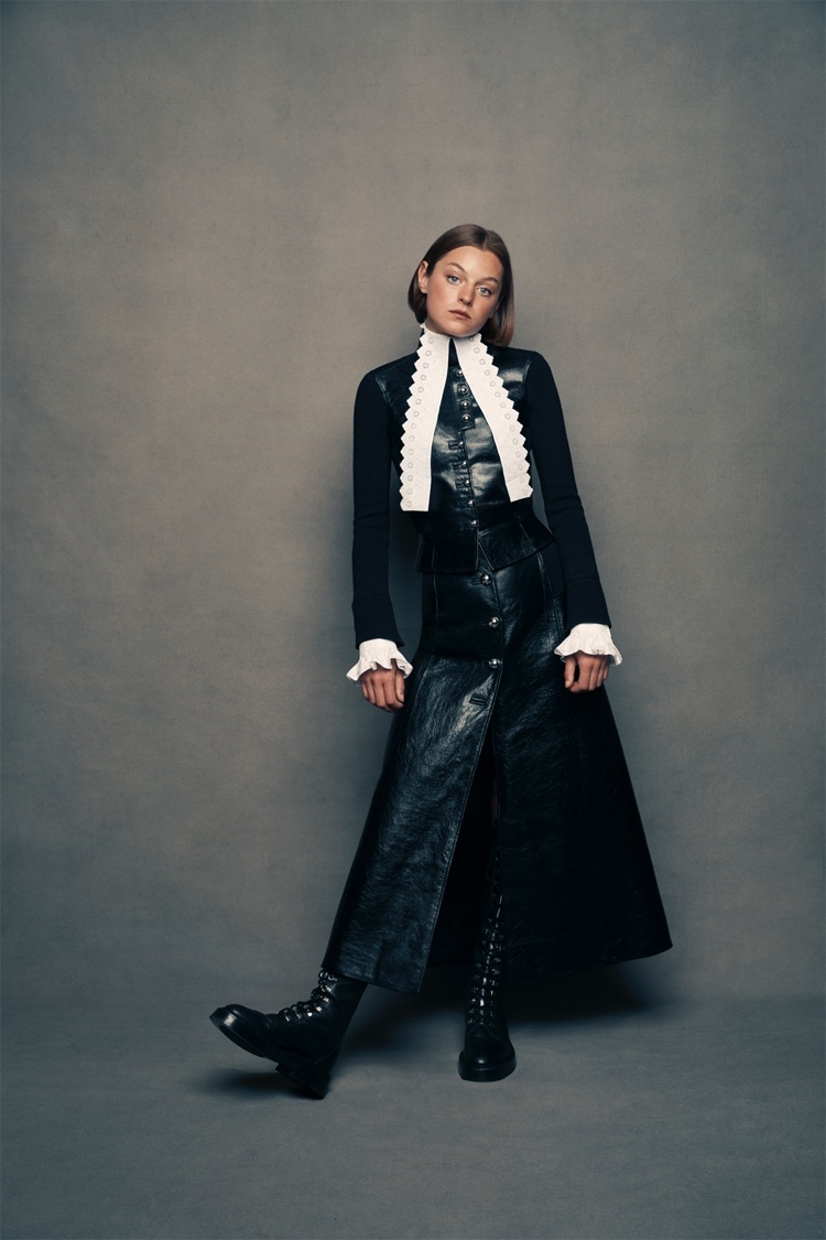 Emma Corrin against the same slate-gray background, wearing chunky black boots, a black leather vest with white-lace detail at the neck, and a matching long skirt with silver buttons. She leans casually to her left side.