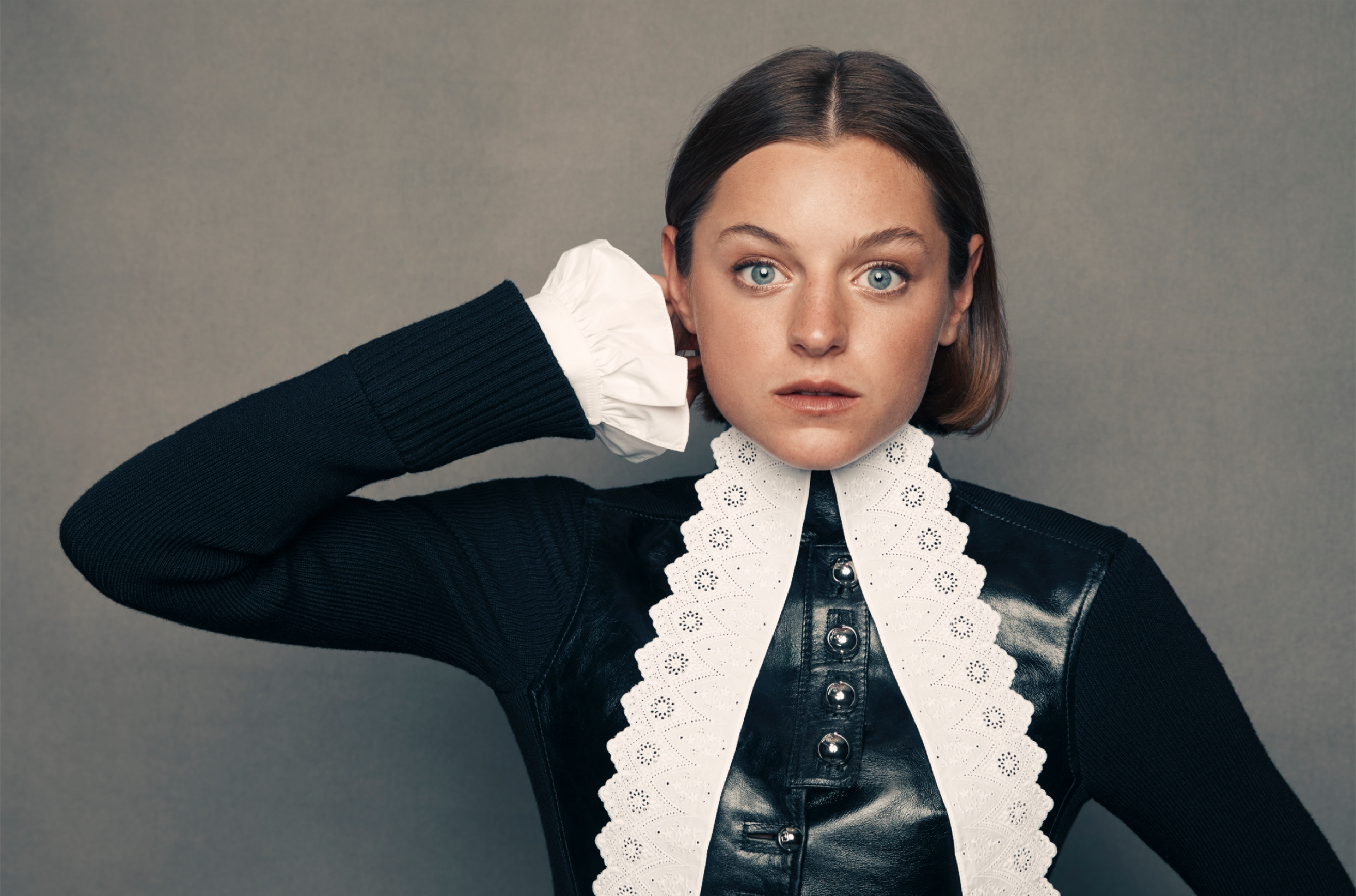 A portrait of Emma Corrin set against a slate-gray background. She wears a striking black leather and lace outfit with long sleeves and a high neckline. She has short cropped brown hair and her blue eyes pierce through the shot.