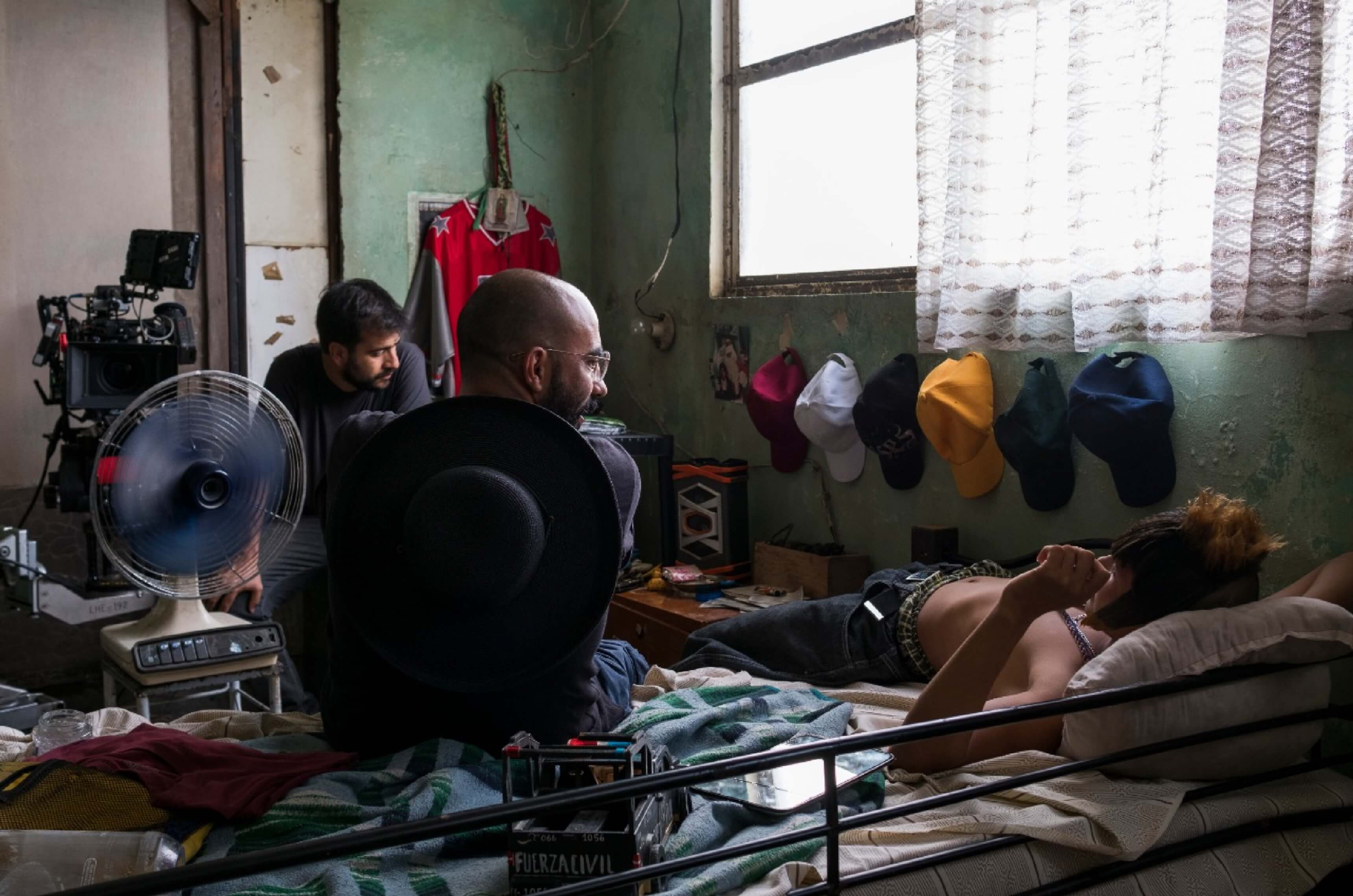 The cinematographer, director, and actor appear in a cramped room with peeling paint, crowded with the character Ulises's personal belongings.