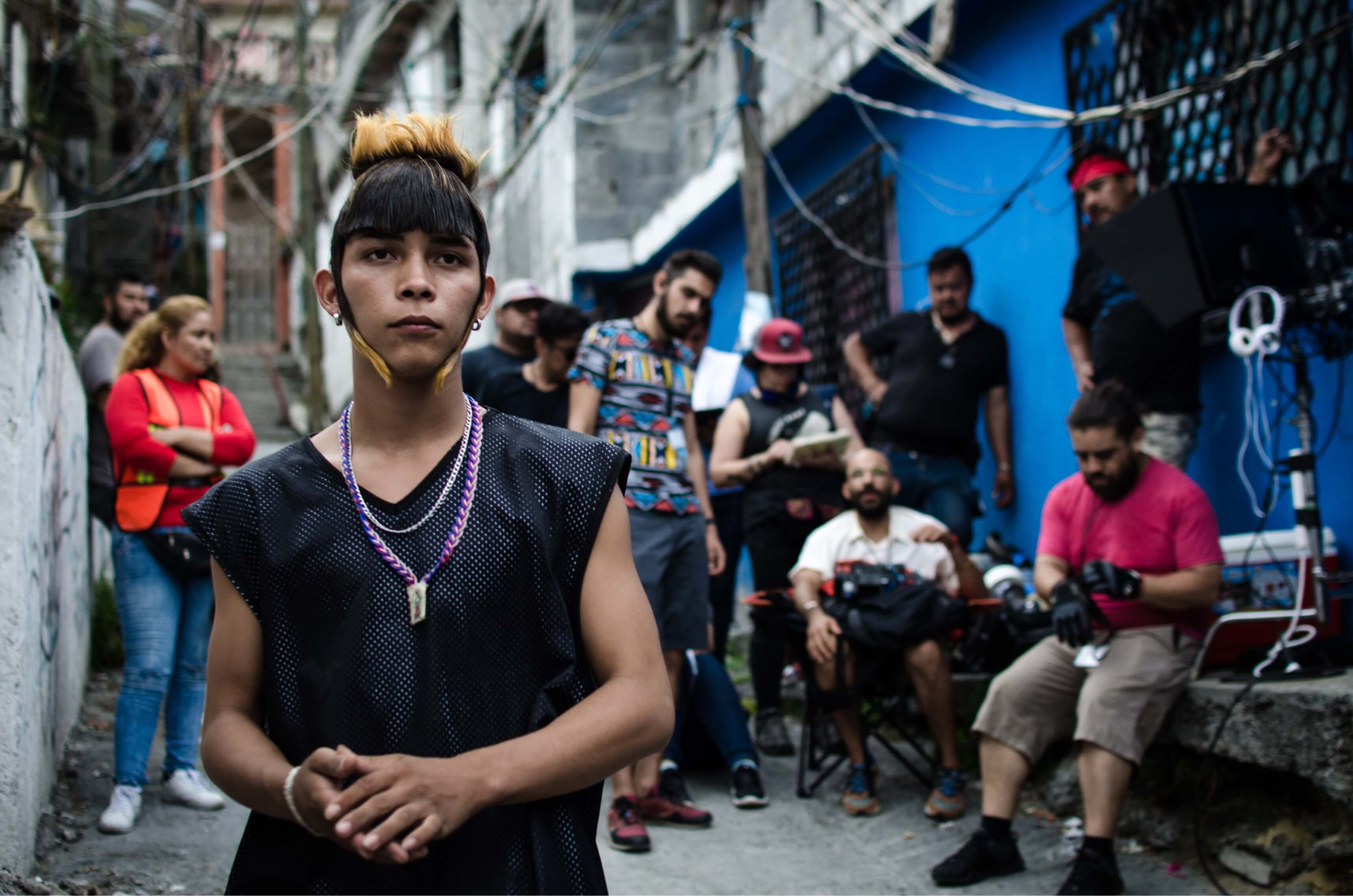 Juan Daniel Garcia Treviño in costume as Ulises, with his signature gelled hairstyle. He stands in a Monterrey alleyway with the film's crew behind him.