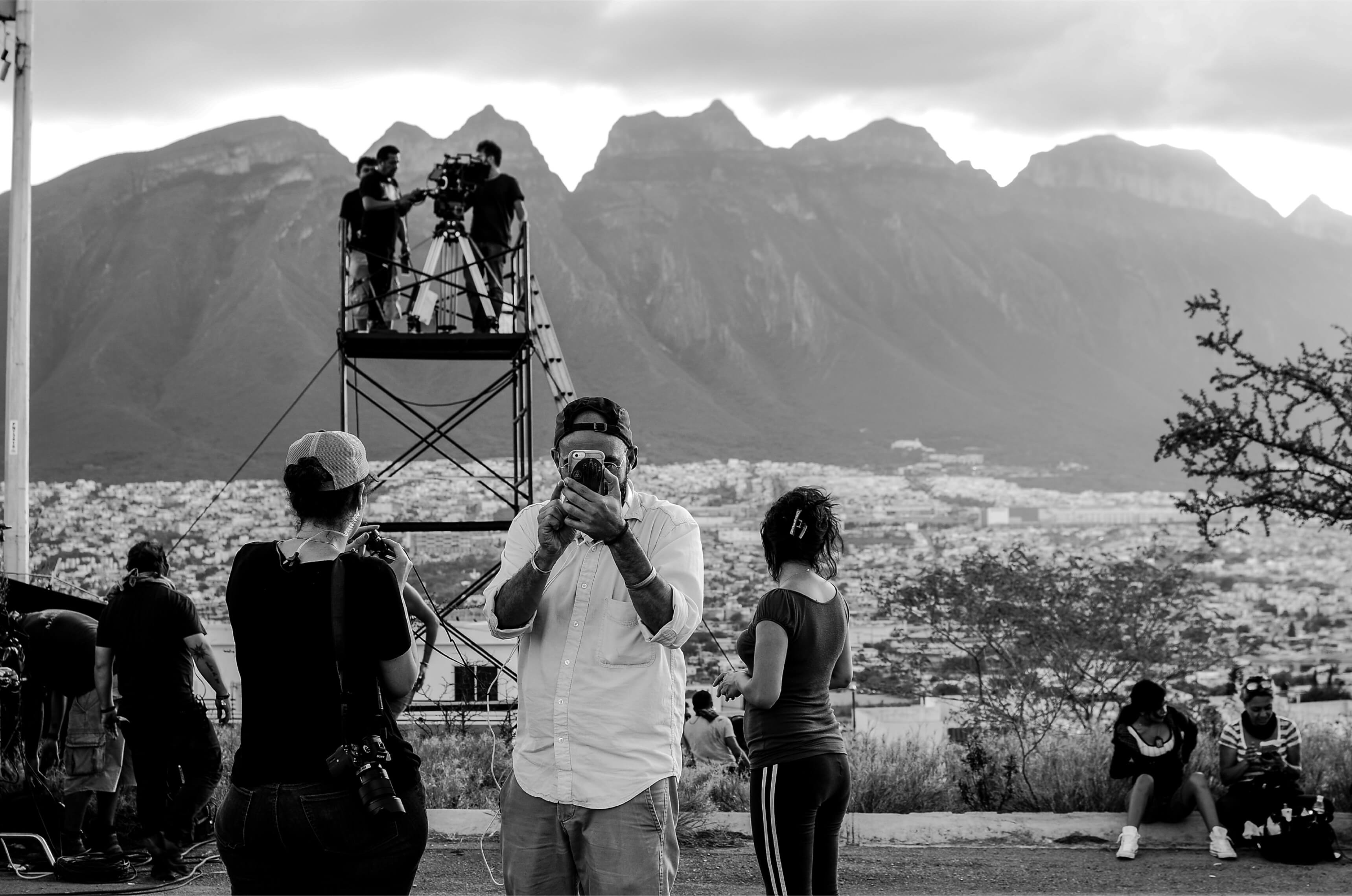 Frías de la Parra holds his camera up to his eye. Behind him, his crew prepares for a scene set against the striking mountains of Monterrey.