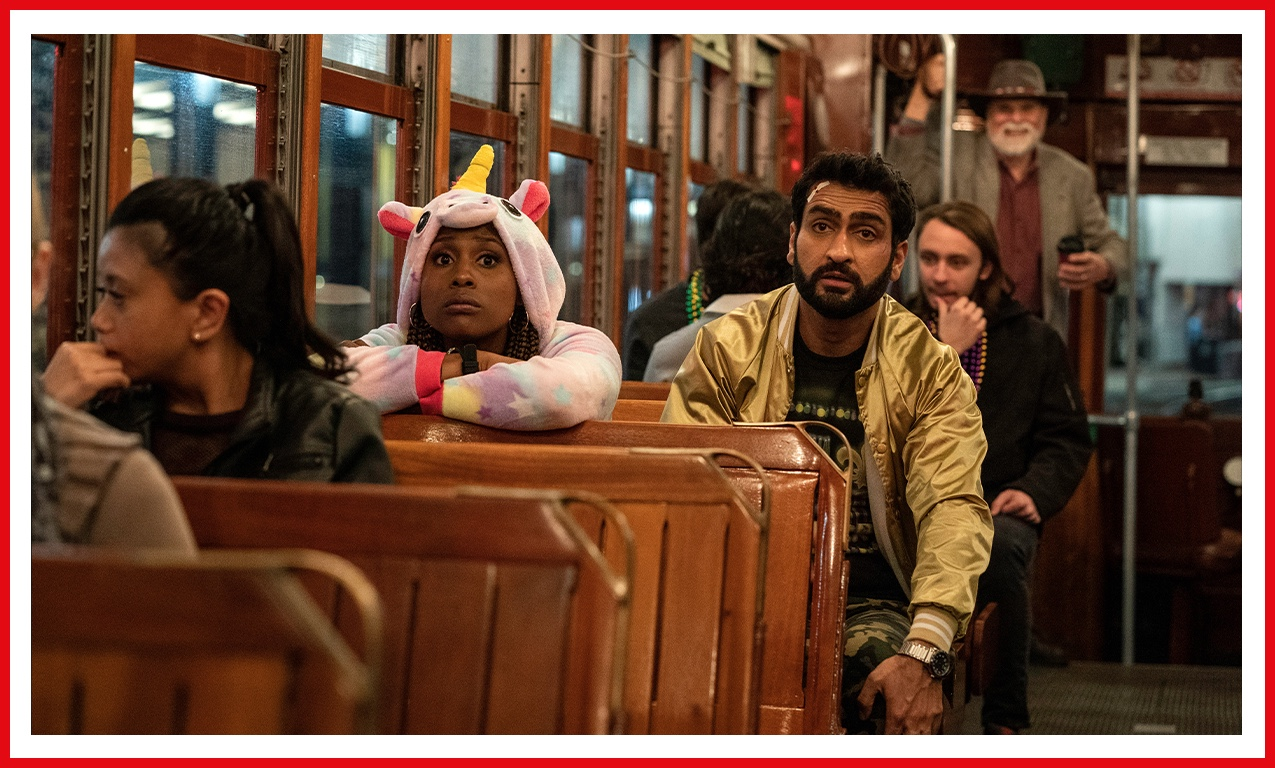 Kumail Nanjiani and co-star Issa Rae are pictured on a streetcar in The Lovebirds. Nanjiani sports a gold bomber jacket and Issa Rae is dressed to impress in a pink unicorn onesie.