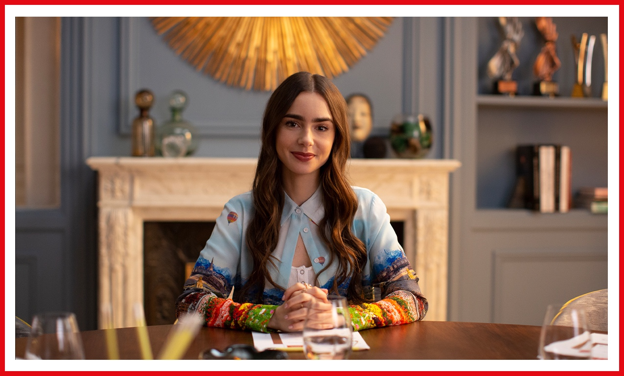 Lily Collins looks eager to impress as Emily in Emily in Paris. Her blue blouse matches the room.