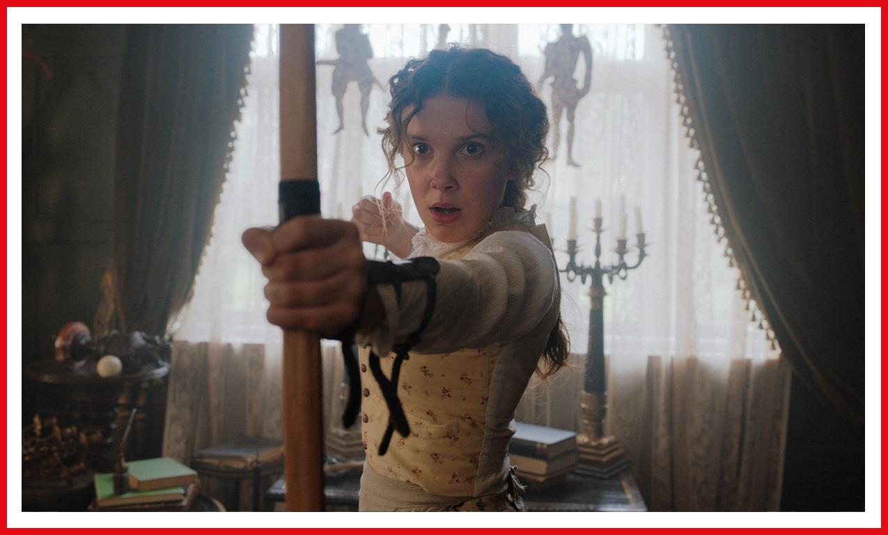 Millie Bobby Brown is prepared for a fight as Enola Holmes. Here, she holds a bow and arrow at the ready.