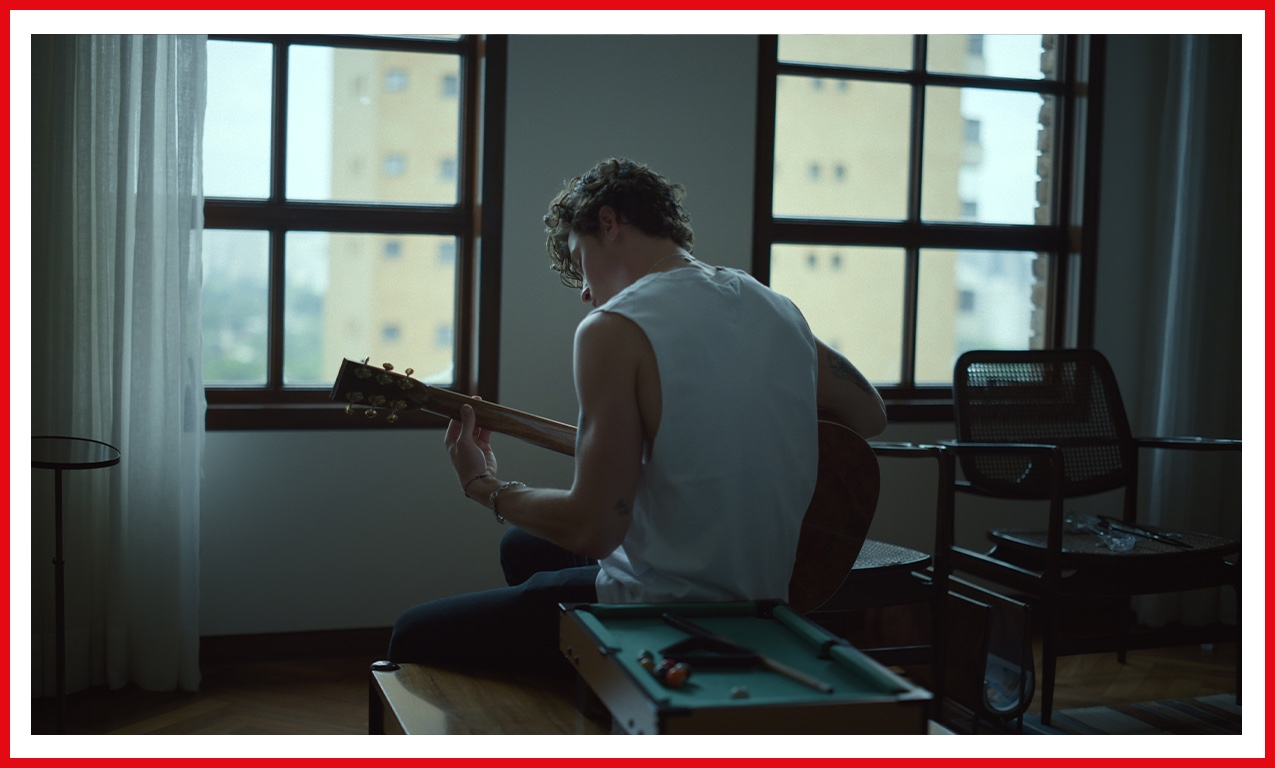 Shawn Mendes pictured from the back, wearing a white tank top, holding his guitar, probably playing something swoon-worthy.