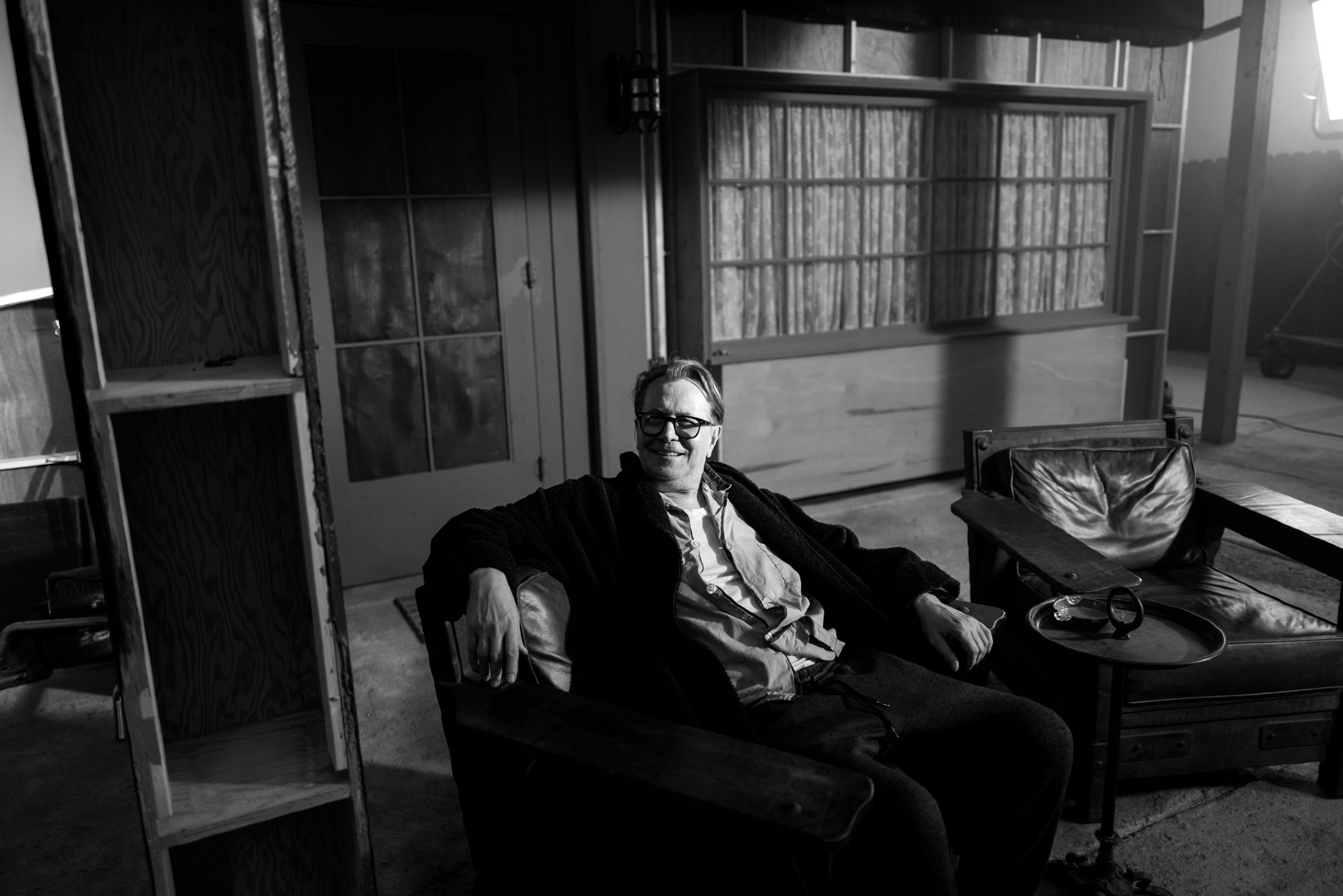 Oldman relaxes in a leather chair on one of the film's interior sets