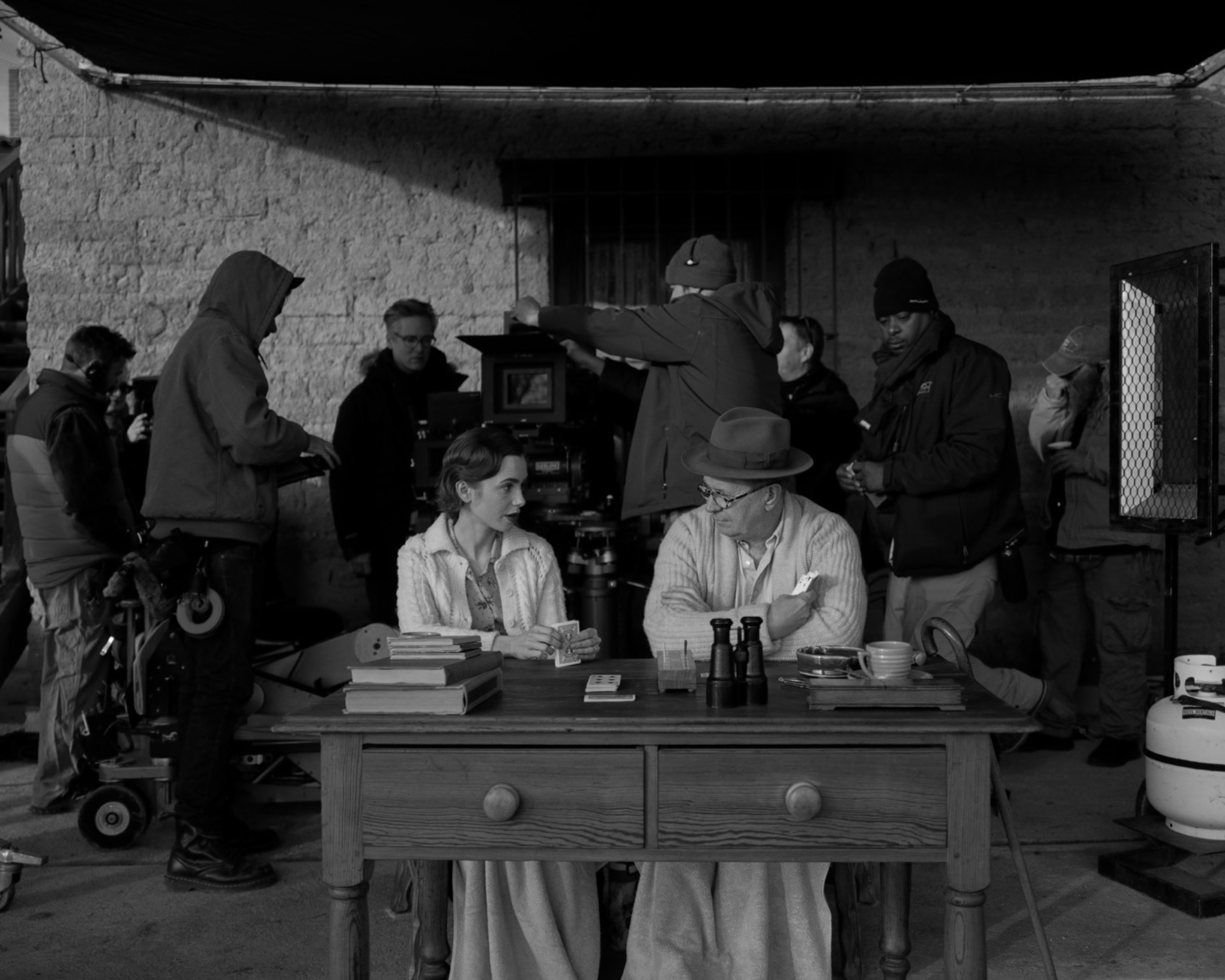The actors sit beside each other at a desk, sporting cable-knit sweaters. Behind them, the crew gets to work.