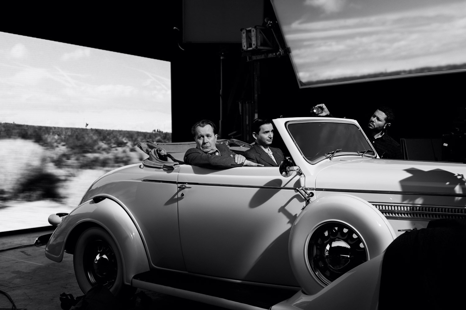 Oldman and Persaud pictured in an open-top automobile with footage of California scenery rolling by on screens around them.