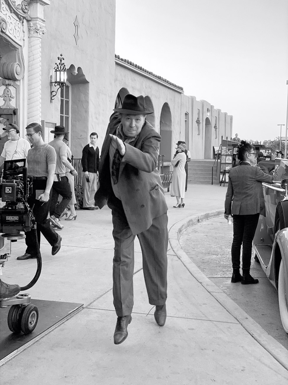Oldman seems to fly toward the camera in suit and tie.
