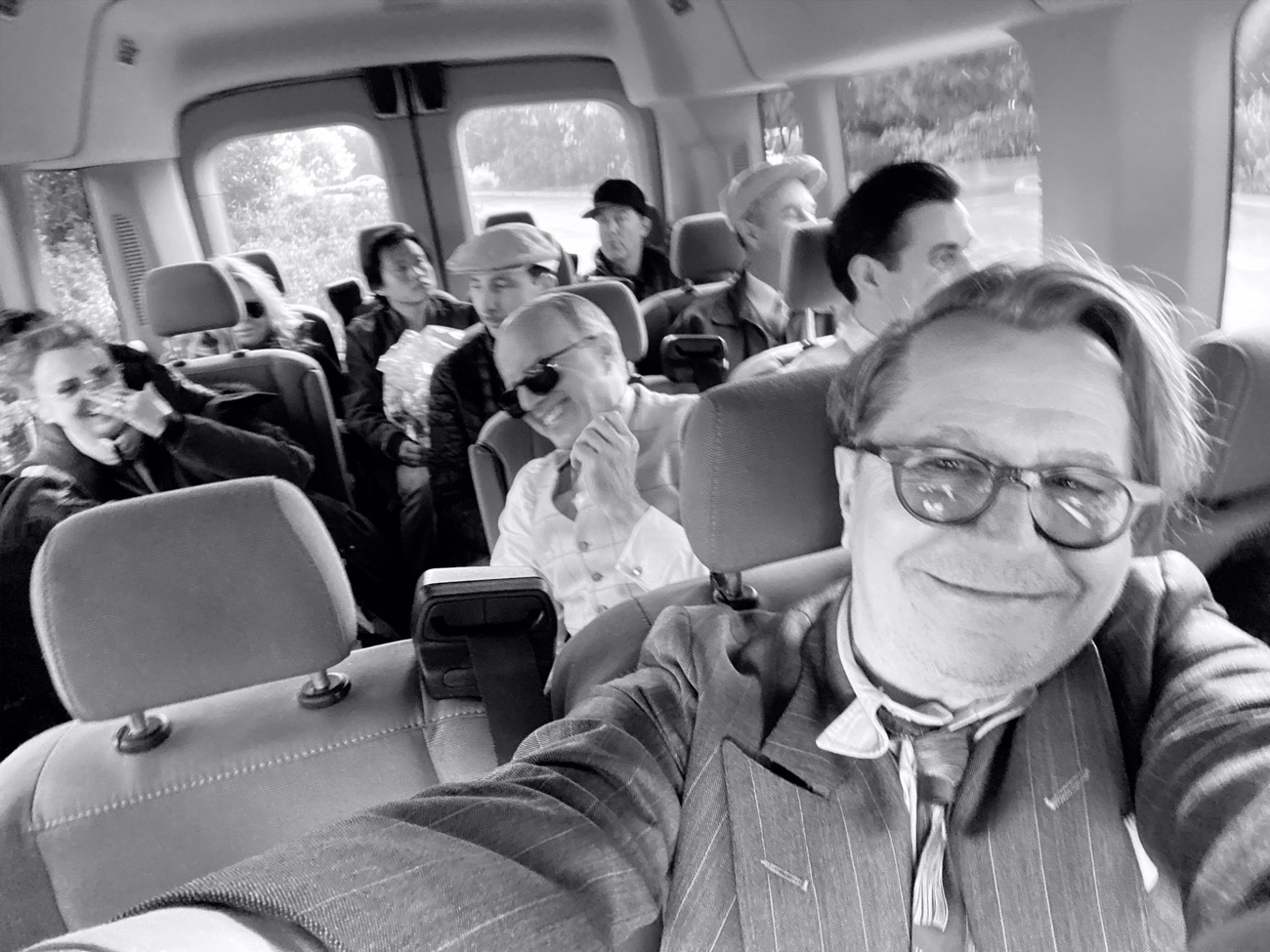 Oldman takes a smiling selfie in a van, with cast and crew enjoying themselves in the background.