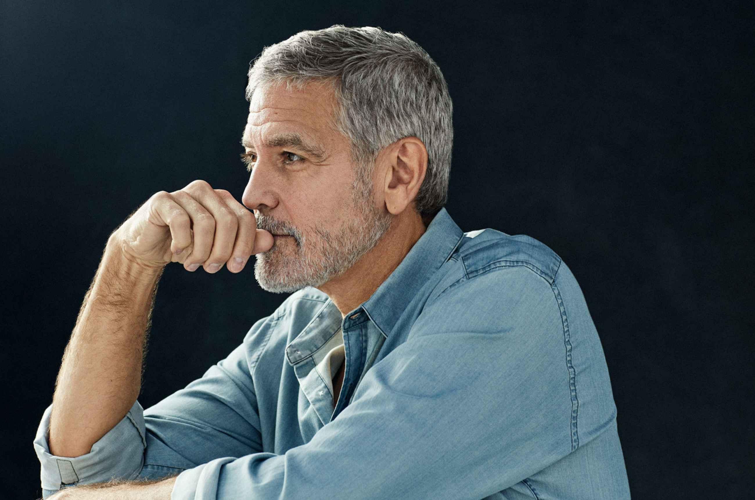 George Clooney looking pensive against a black background. Don't you ever wonder if he's thinking of you?