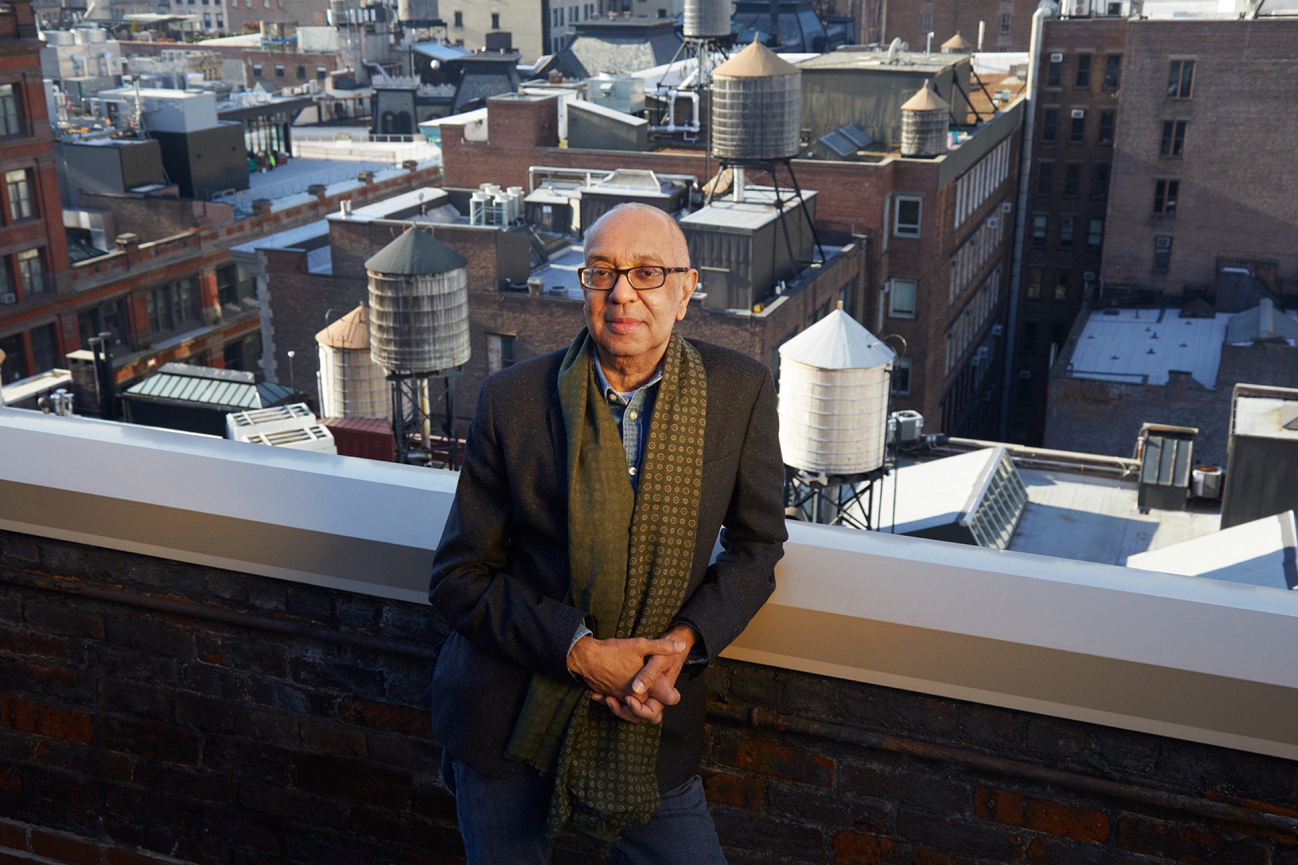 Director George C. Wolfe stands on a New York City rooftop. Behind him: a glimpse of the city.