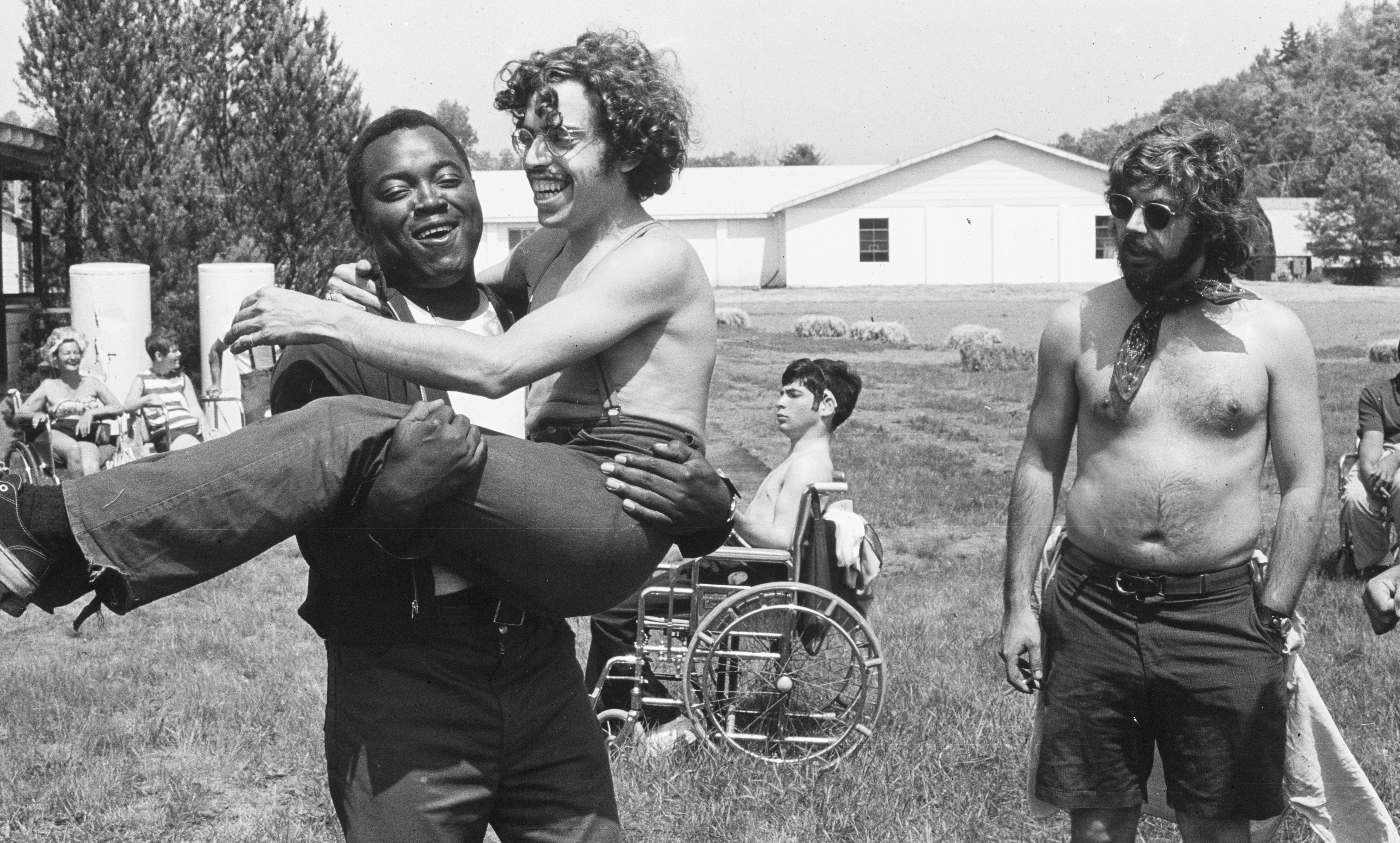 A black-and-white photograph of teenagers at camp. In the foreground, one camper carries his wheelchair-bound friend, both laughing, while another camper, shirtless and sporting a neckerchief, looks on.