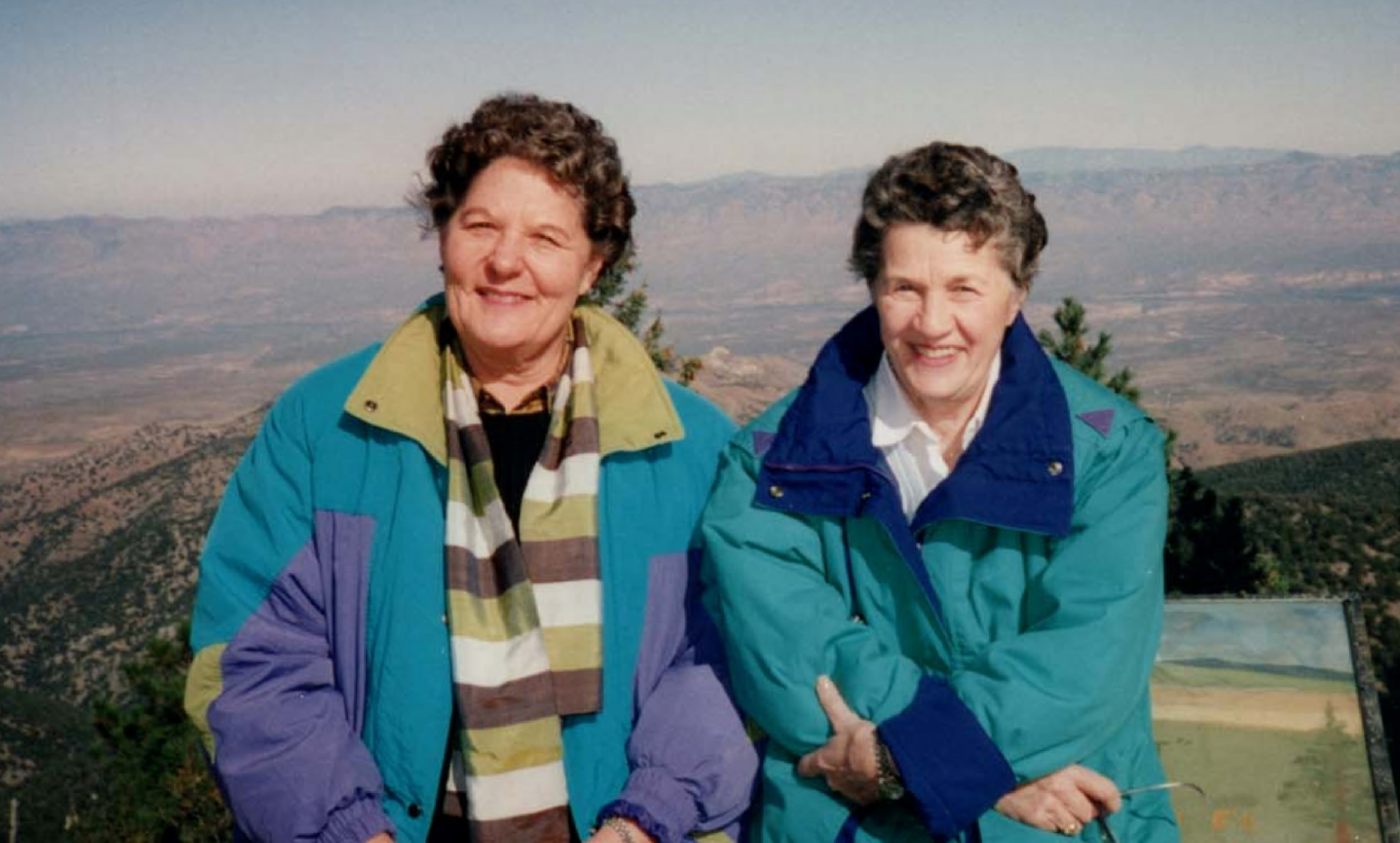 Henschel and Donahue pose smiling in front of scenic mountains in this faded photograph. The pair wear windbreakers in classic 80s colors.