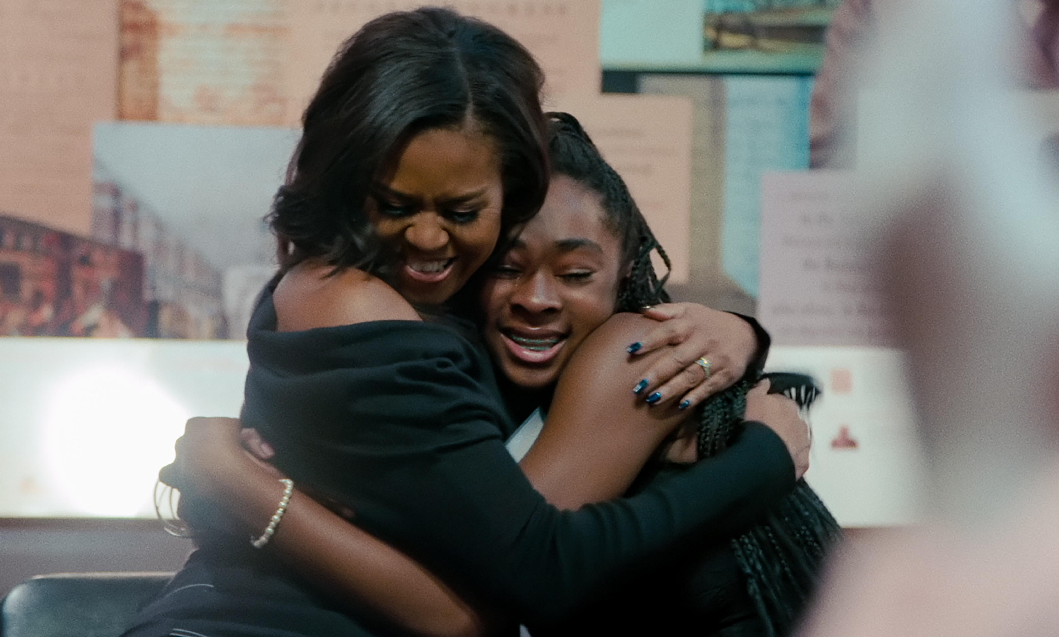 The first lady smiles as she pulls a student into a tight hug.
