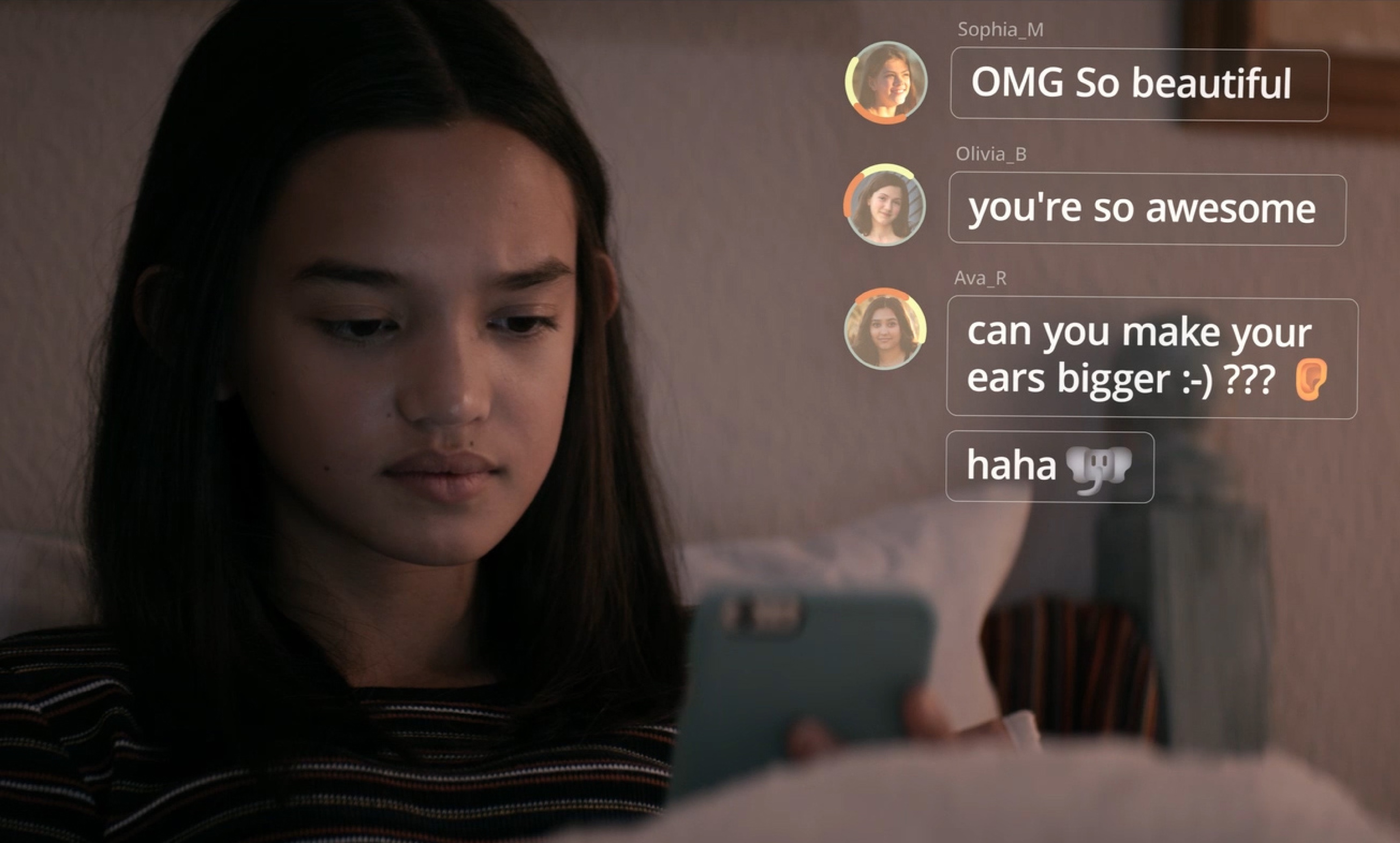 """A young girl is pictured in her room, looking at her phone. Social media comments are superimposed on the frame, reading """"OMG So beautiful""""; """"you're so awesome""""; and """"Can you make your ears bigger?"""""""