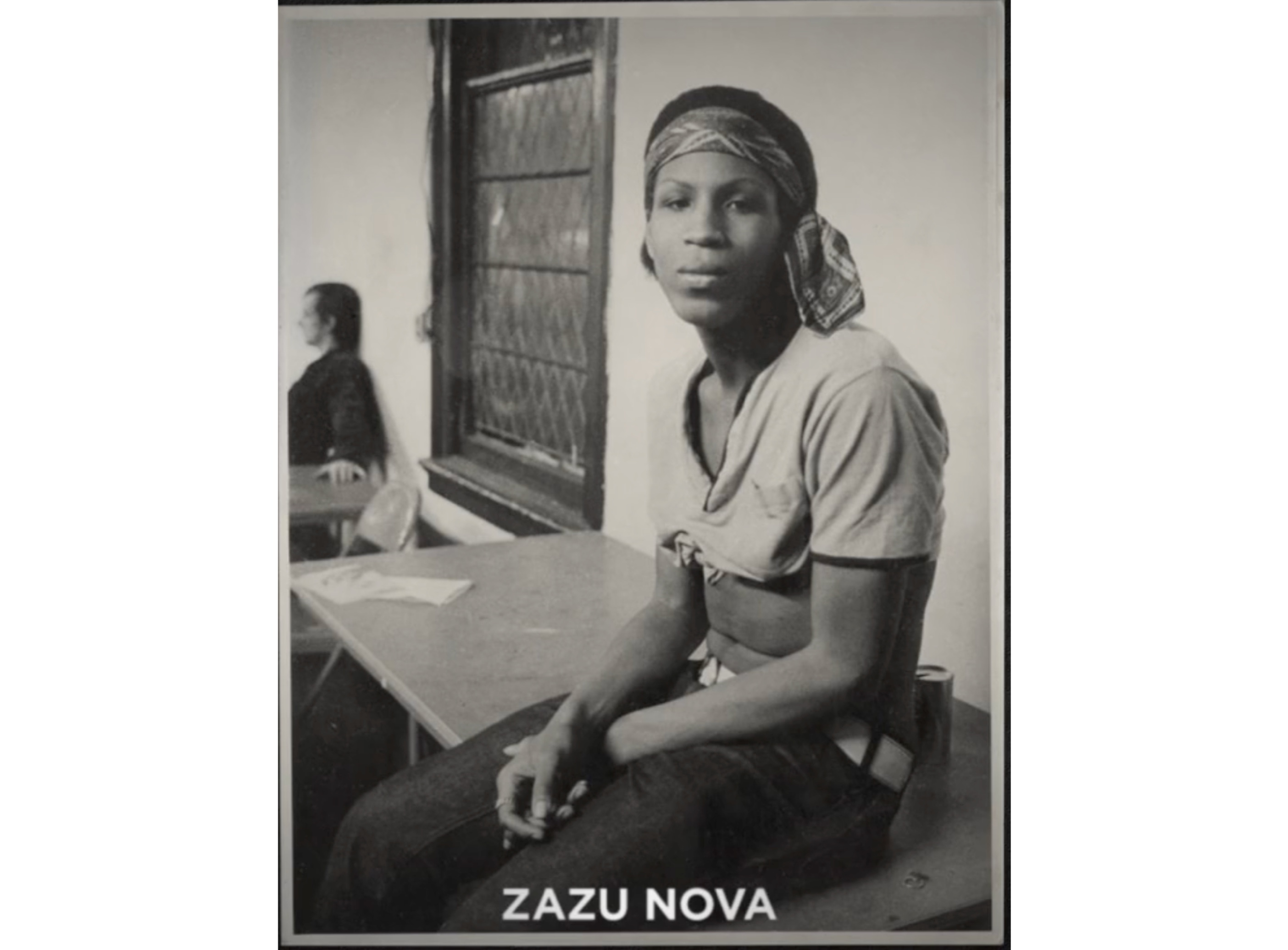 An archival, sepia-toned photo of Zazu Nova perched on a desk, looking serious and casually stylish in a cropped t-shirt and bandana.