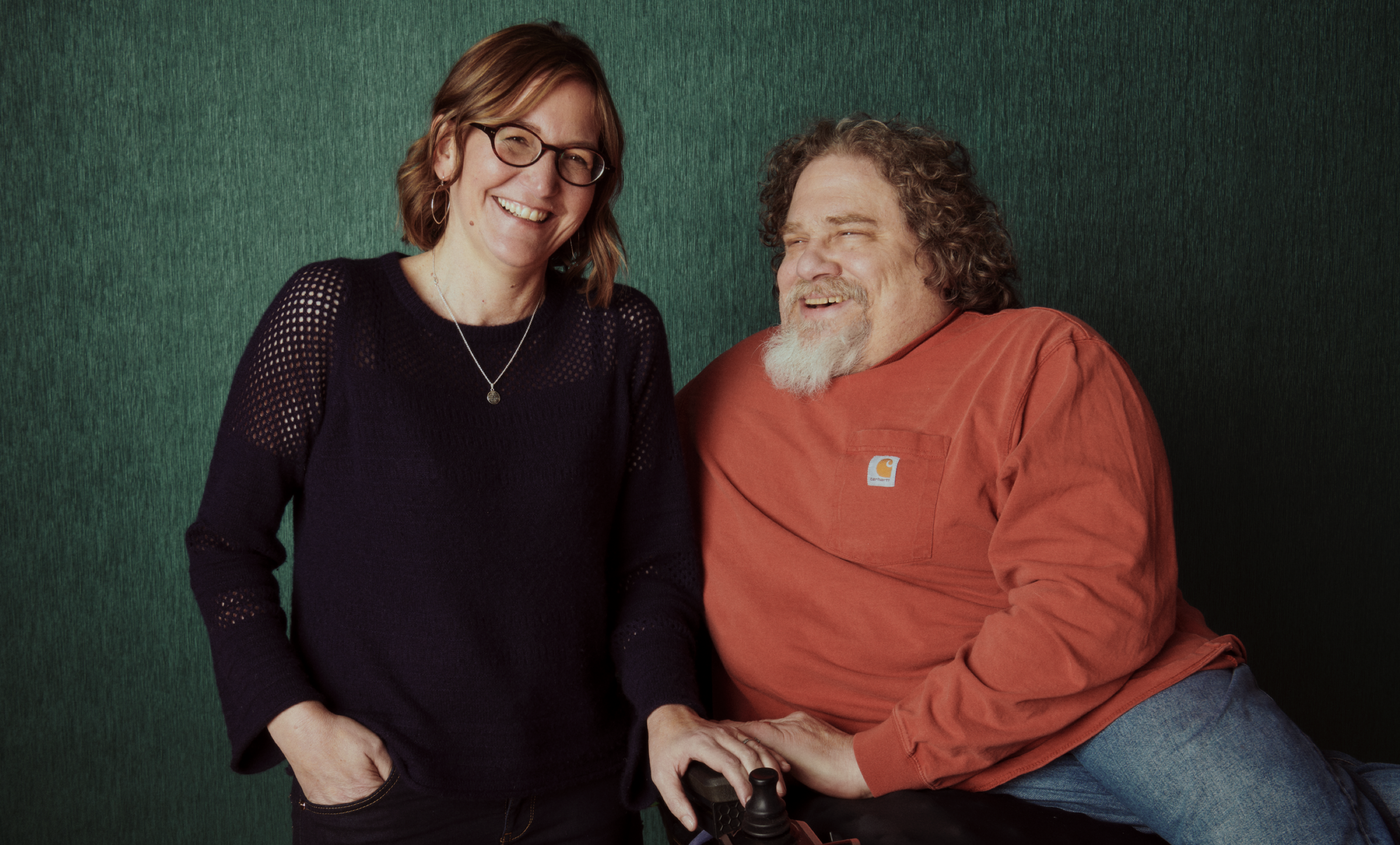 Crip Camp co-directors Nicole Newnham and Jim LeBrecht pose, laughing, in front of a green backdrop.