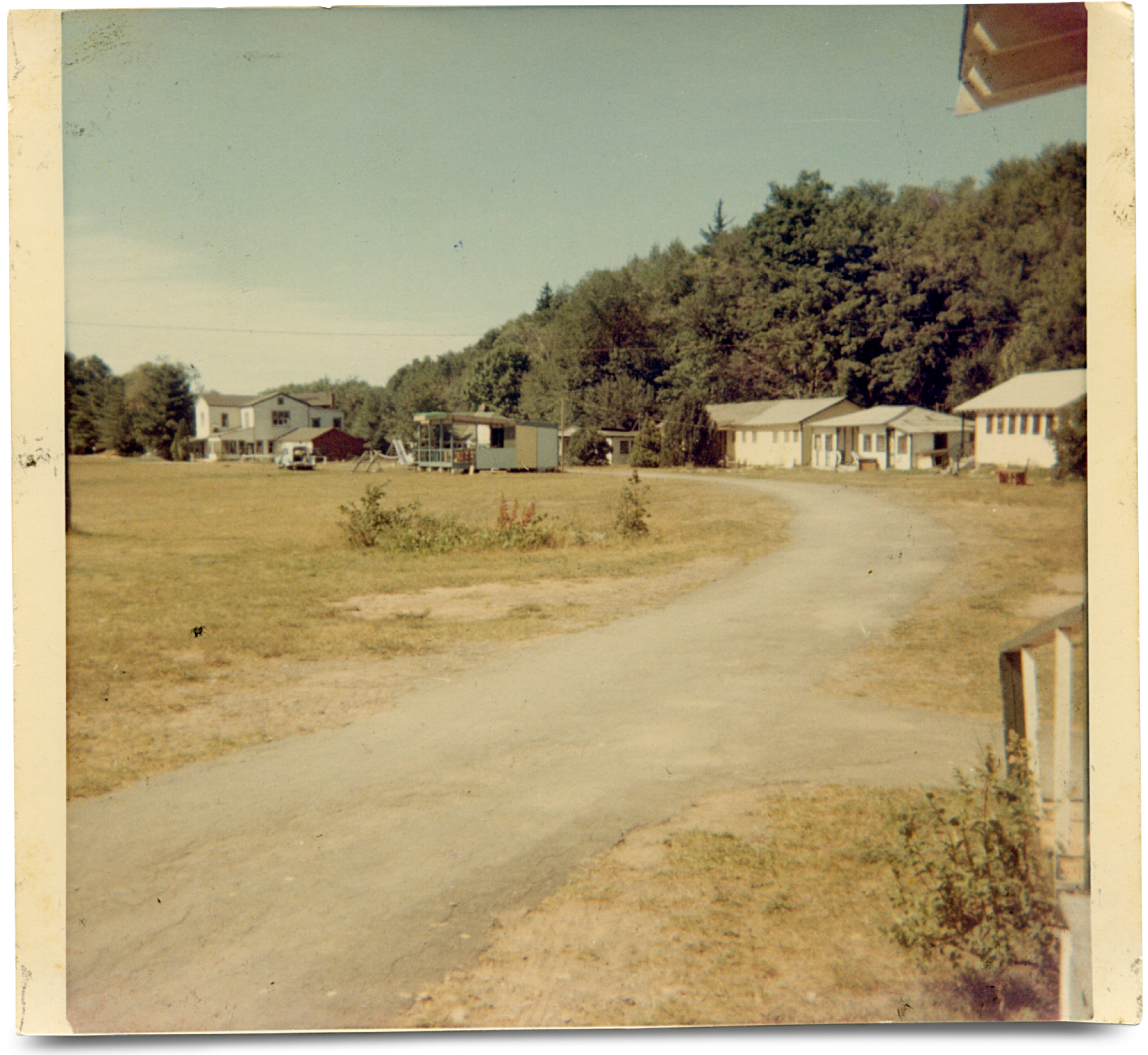 Camp Jened is pictured in a sun-faded photograph. Low, white buildings line the paved road through camp, and trees rise up behind them.