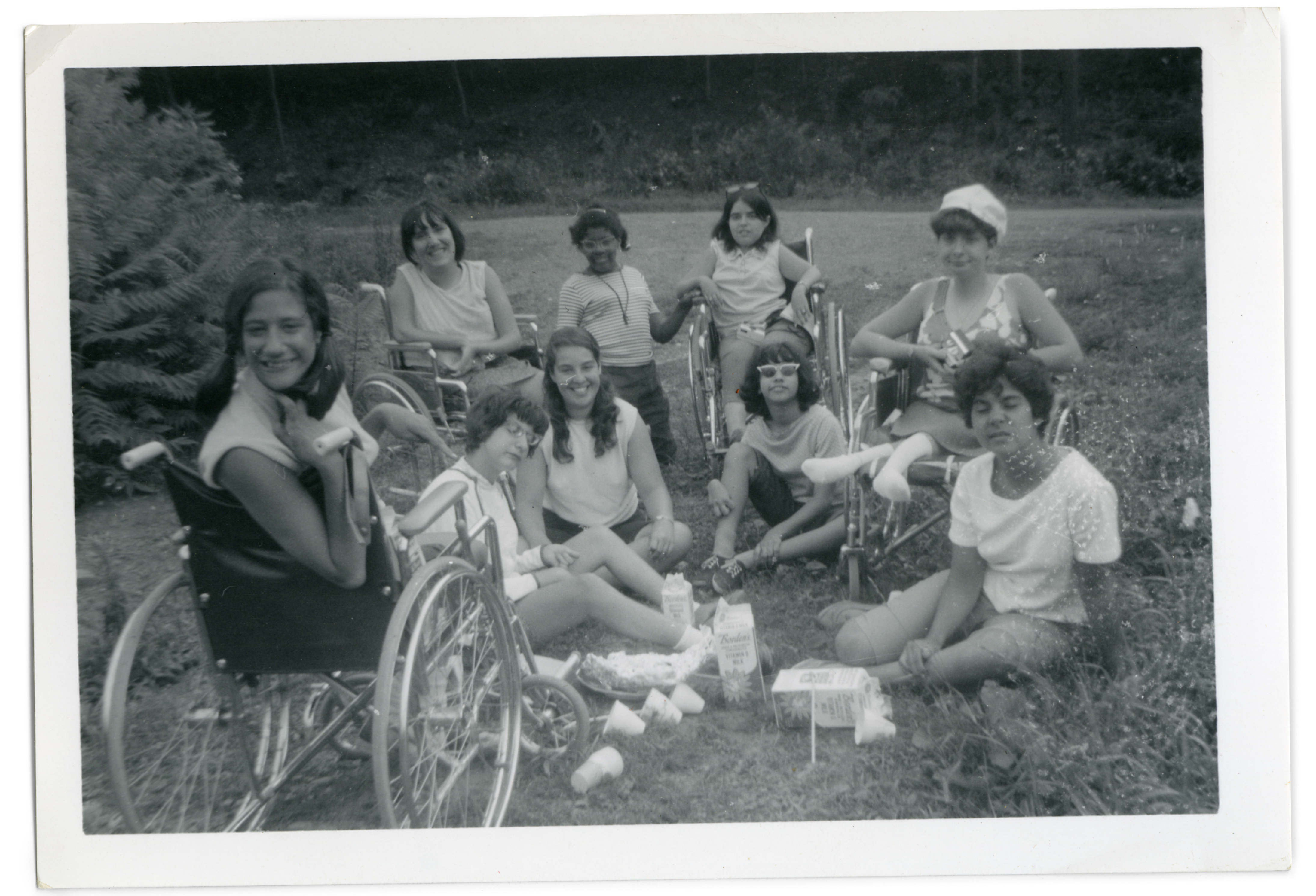 In an old photograph, teens sit in a circle on the grass, enjoying a summer day.
