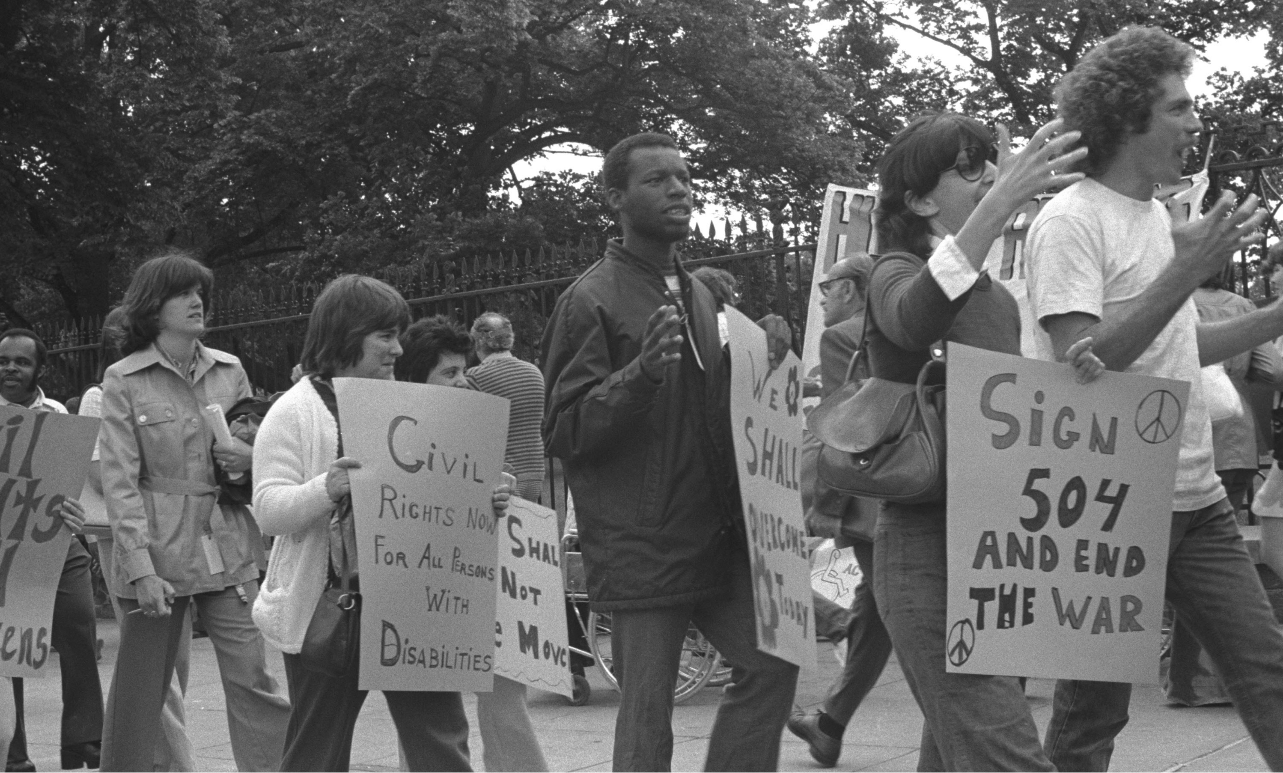"Demonstrators are pictured in black and white, holding signs that read ""Civil Rights Now for All Persons with Disabilities"" and ""Sign 504 and End the War."""